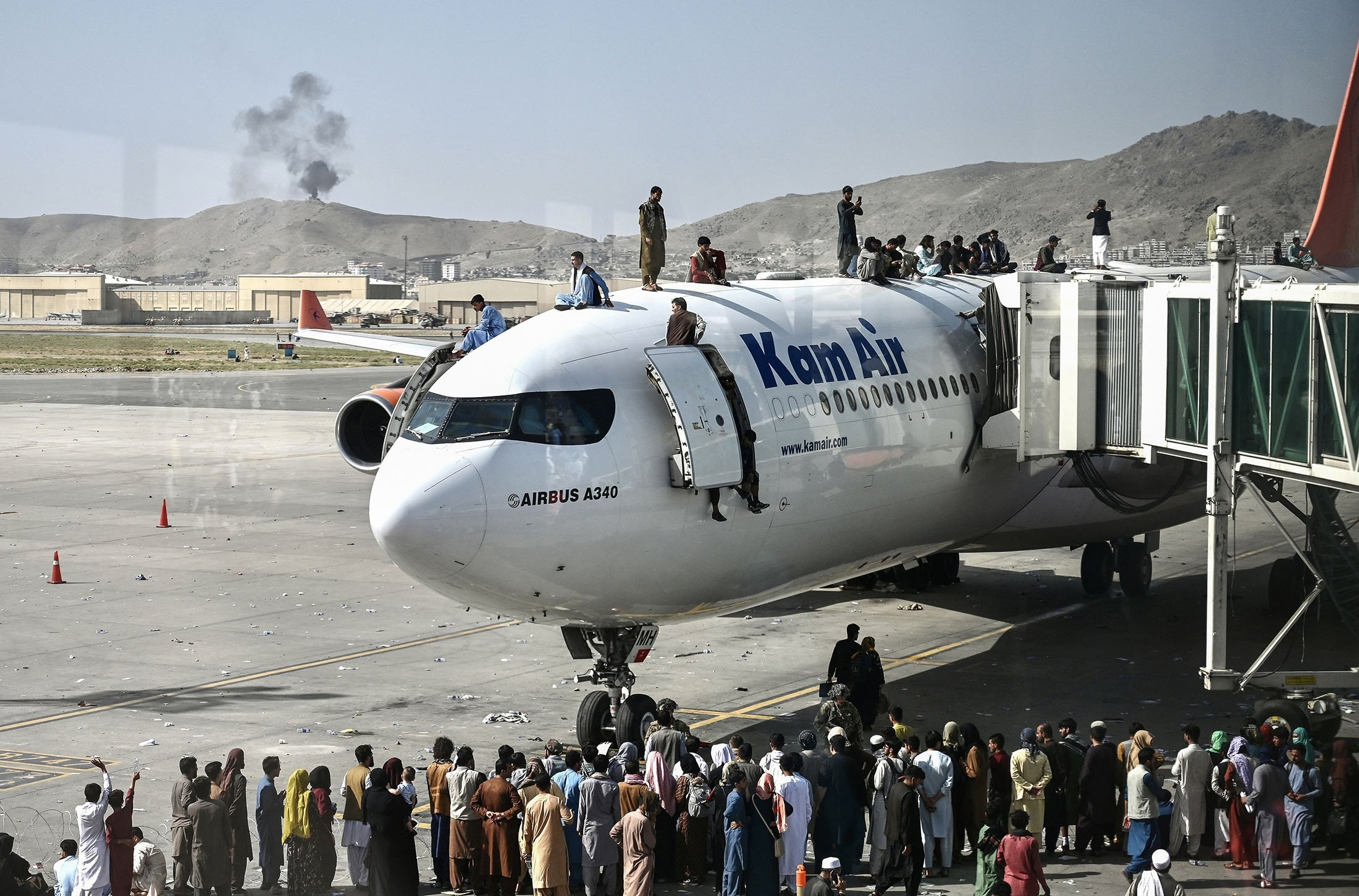 Afghan people climb atop a plane as they wait at the Kabul airport, Aug. 16, 2021. (AFP Photo)