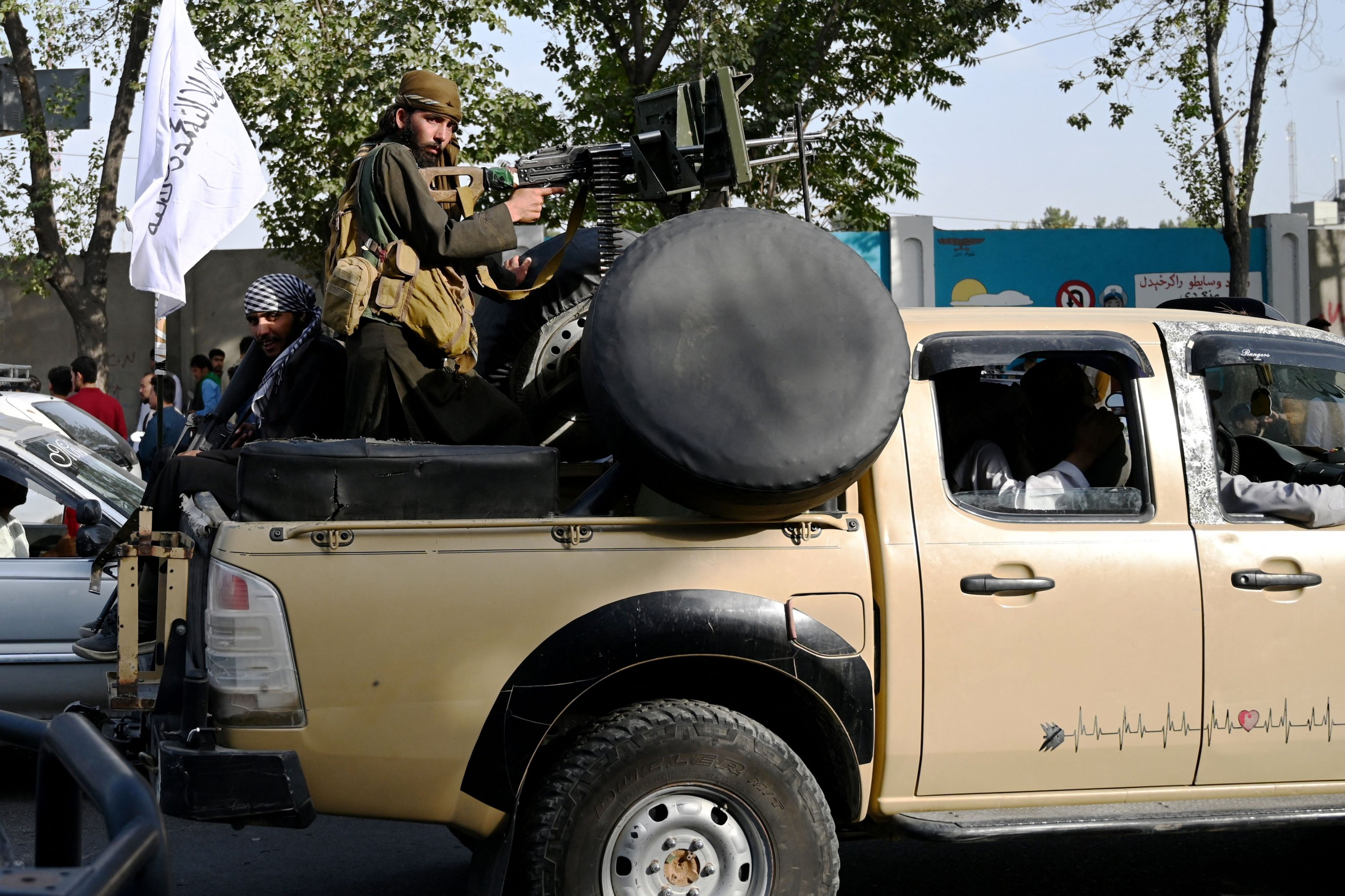 Taliban fighters travel with weapons mounted on a vehicle after the group's military takeover in Kabul, Afghanistan, Aug. 19, 2021. (Photo by WAKIL KOHSAR via AFP)