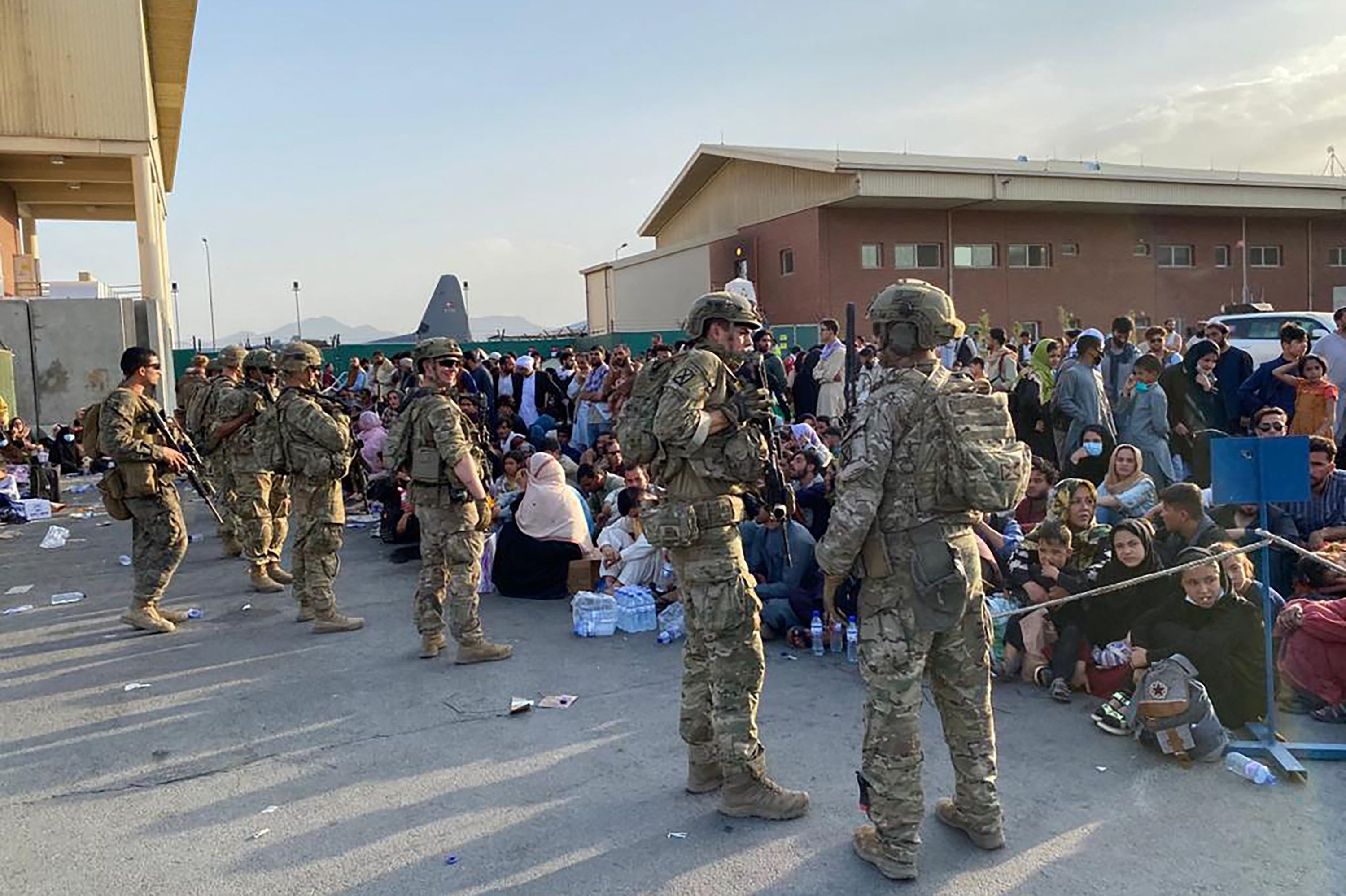 U.S. soldiers stand guard as Afghan people wait to board a U.S. military aircraft to leave Afghanistan after the Taliban's military takeover, at the military airport in Kabul, Afghanistan, Aug. 19, 2021. (Photo by Shakib RAHMANI via AFP)