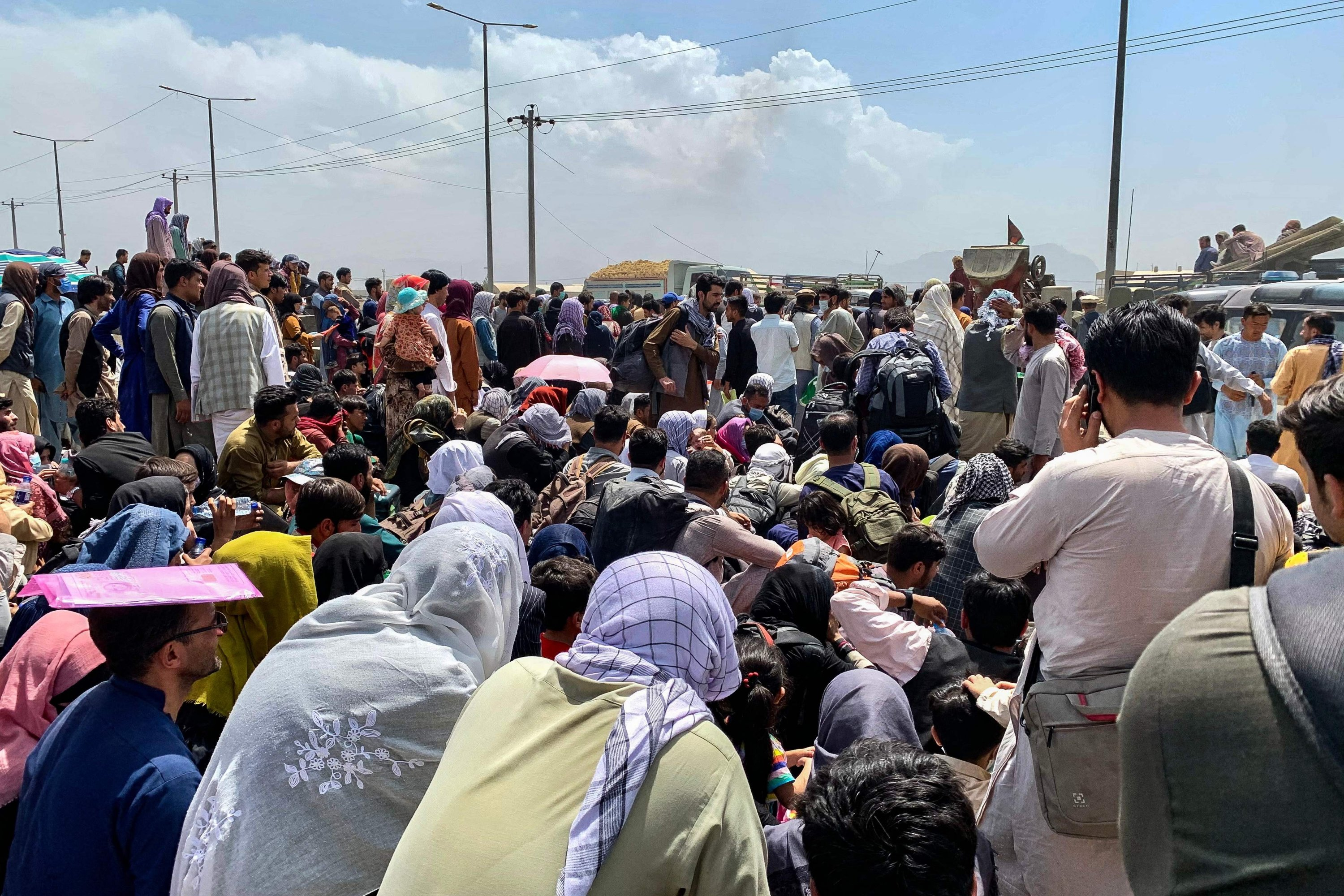 Afghan people gather along a road as they wait to board a U.S. military aircraft to leave the country, at a military airport in Kabul, Afghanistan, Aug. 20, 2021, days after the Taliban's military takeover of the country. (AFP Photo)