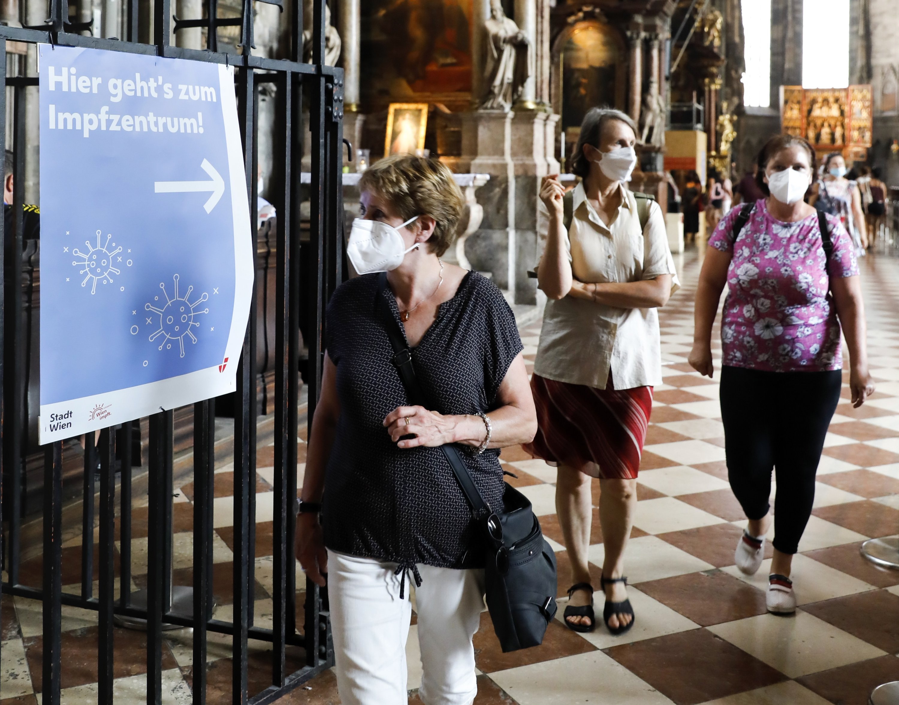Vaccinations against the COVID-19 disease are offered now in one of Austria's most iconic buildings, the St. Stephan's Cathedral in the city center of Vienna, Austria, Friday, Aug. 13, 2021. There is a sign on the left, which says translated: 'this way to the vaccination center.' (AP Photo)