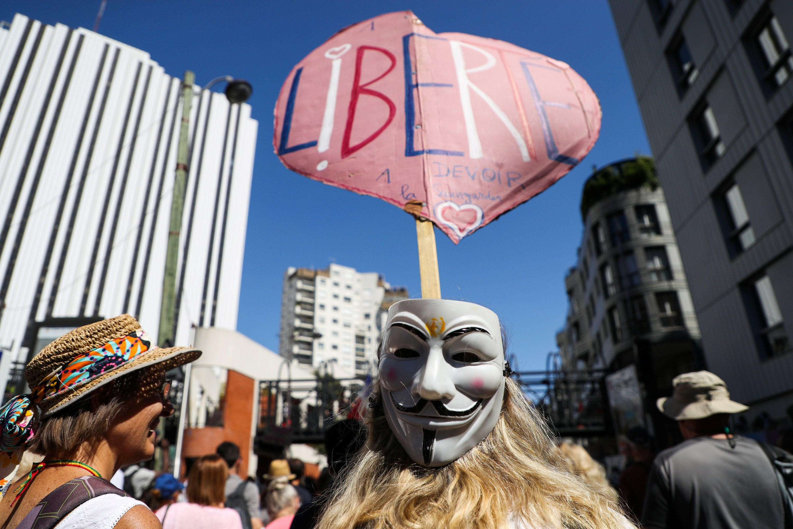 A protester with an anonymous mask holds a placard reading 'Liberty' during a demonstration called by the French nationalist party 'Les Patriotes' (The Patriots) against France's restrictions, including a compulsory health pass, to fight the coronavirus outbreak, in Paris, France, Aug. 14, 2021. (Reuters Photo)