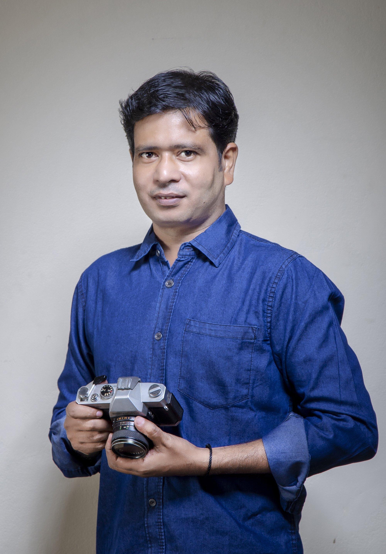 Bangladeshi photojournalist Mohammed Shajahan poses with his camera. (AA Photo)