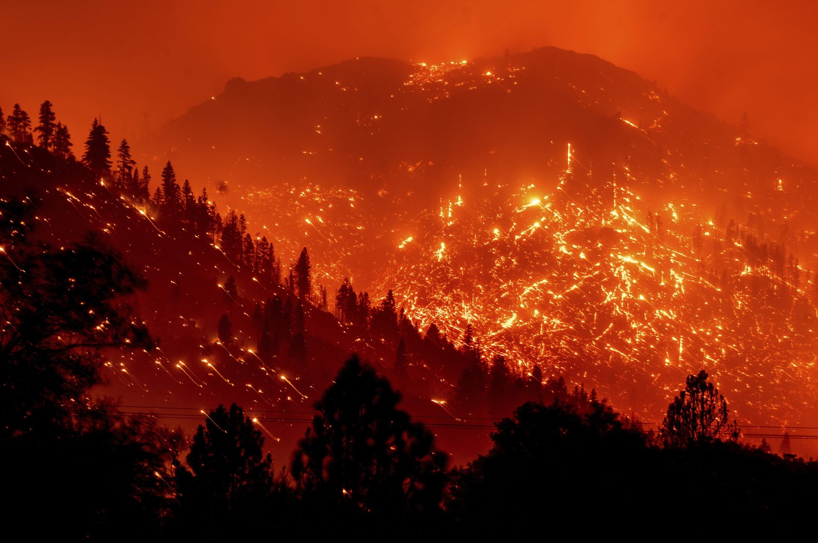 Seen in a long exposure photograph, embers light up hillsides as the Dixie Fire burns near Milford in Lassen County, California, U.S., Aug. 17, 2021. (AP Photo)