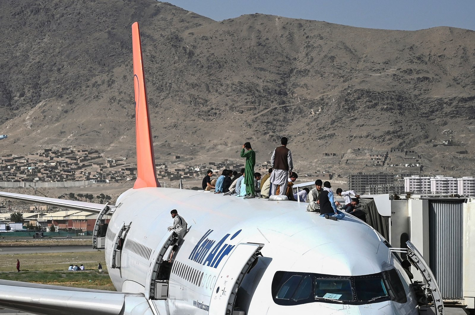 Afghan people climb atop a plane as they wait at Kabul Hamid Karzai International Airport in Kabul, Afghanistan, Aug.16, 2021. (AFP Photo)