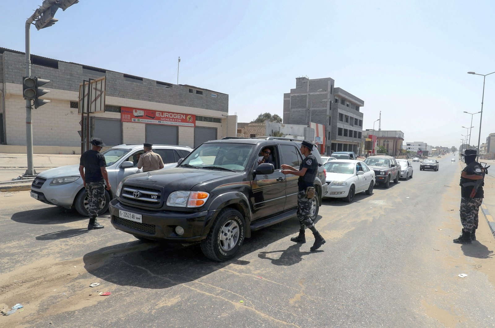 Libyan security officers run a checkpoint to verify the implementation of a total curfew the authorities announced a day earlier to mitigate the spread of the COVID-19 pandemic, in the capital Tripoli, Libya, Aug. 7, 2021. (AFP Photo)
