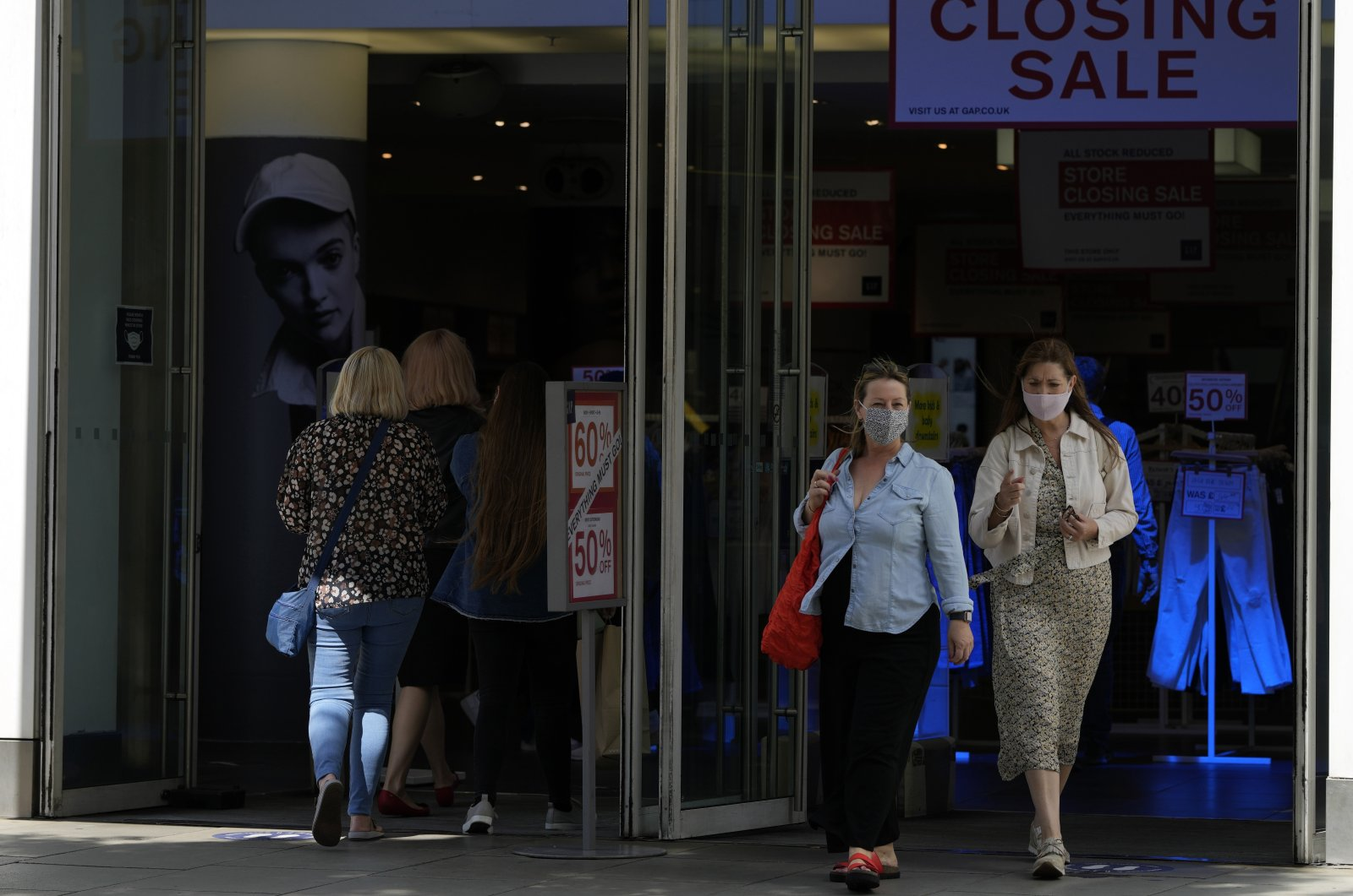 Two women walk from a shop while wearing face masks against the coronavirus in London, U.K., Friday, Aug. 6, 2021. (AP Photo)