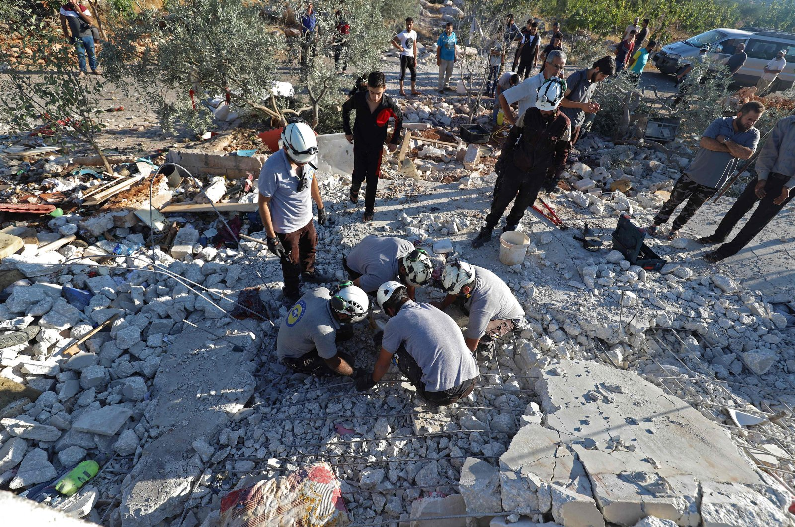 Members of the Syrian Civil Defence (White Helmets) search through the rubble of a building that was knocked down by Syrian regime forces' bombardment in the town of Balashun in the Jabal al-Zawiya region in the south of Syria's northwestern Idlib province, on Aug. 19, 2021. (Photo by Abdulaziz KETAZ / AFP)