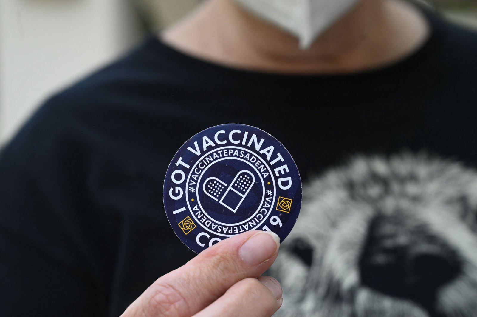 """A woman holds up a sticker after getting her third """"booster"""" dose of COVID-19 vaccine at a clinic hosted by The Tournament of Roses in partnership with the Pasadena Public Health Department, at Tournament House in Pasadena, California, U.S., Aug. 19, 2021. (AFP Photo)"""