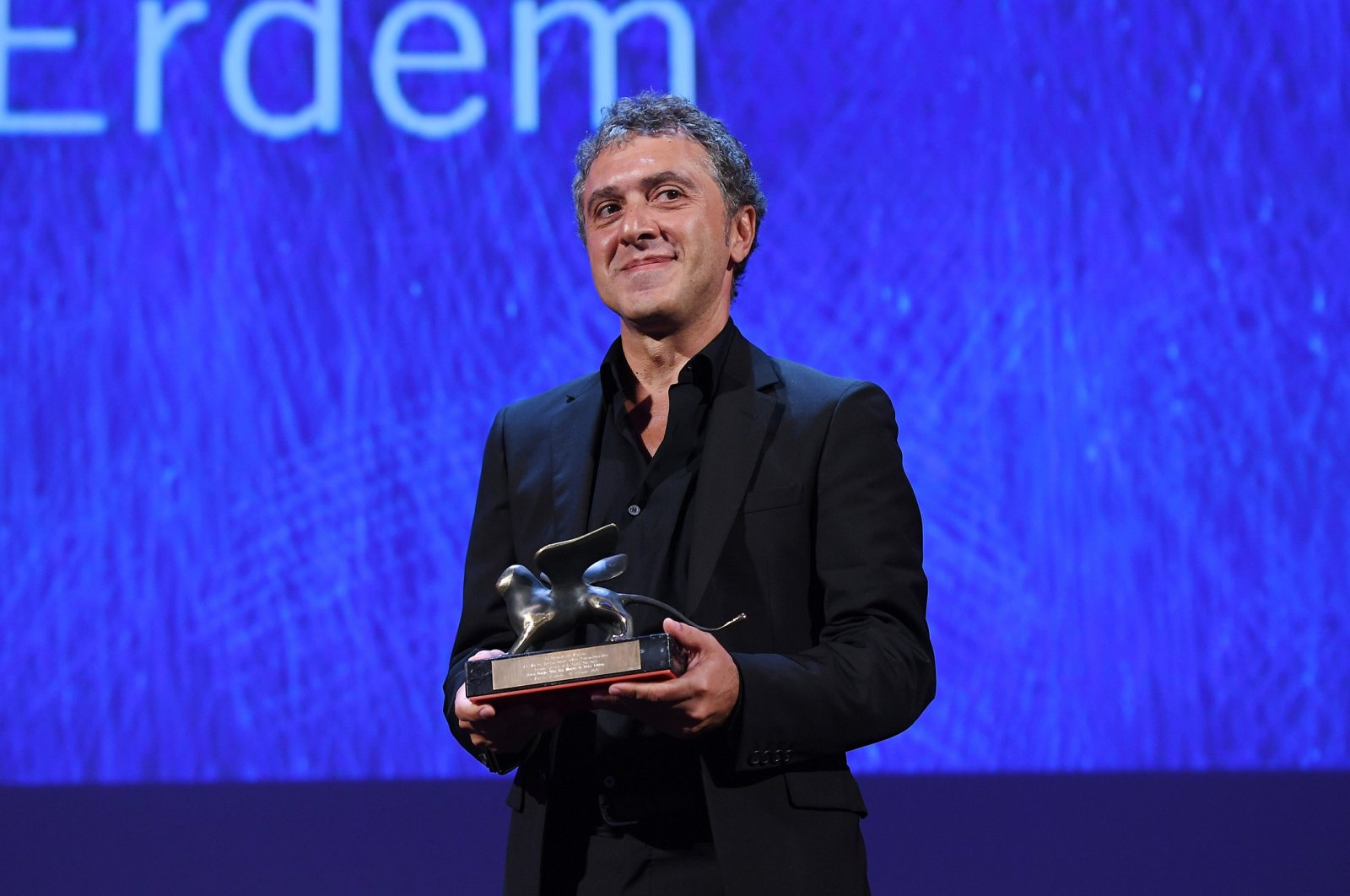 """Director Reha Erdem poses with the Special Orizzonti Jury Prize for his movie """"Koca Dünya"""" (""""Big Big World"""") during the closing ceremony of the 73rd Venice Film Festival at Sala Grande on Sept. 10, 2016, in Venice, Italy.  (Getty Images)"""