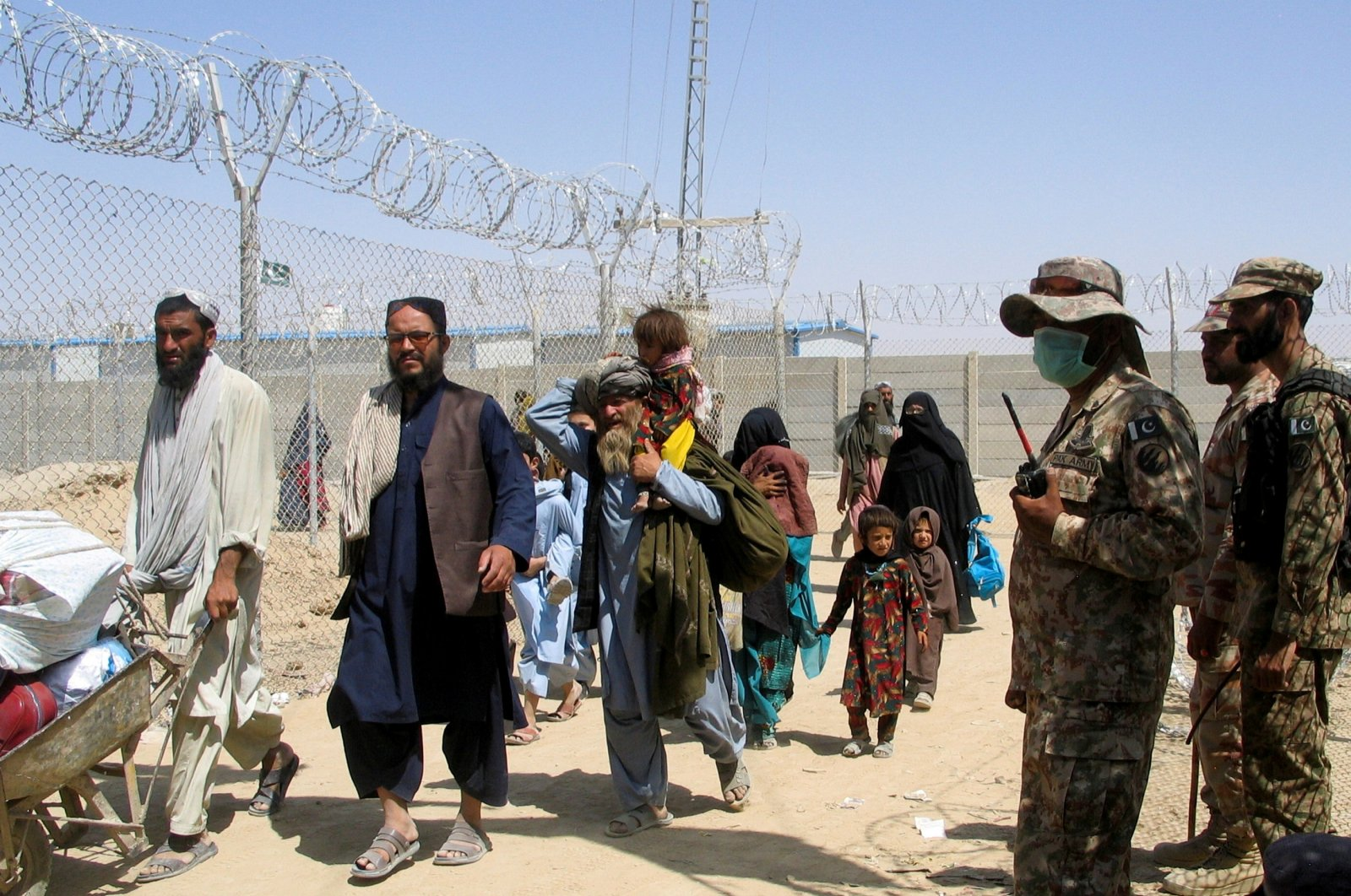 People arriving from Afghanistan make their way through the Friendship Gate crossing point at the Pakistan-Afghanistan border town of Chaman, Pakistan, Aug. 19, 2021. (Reuters/Saeed Ali Achakzai)