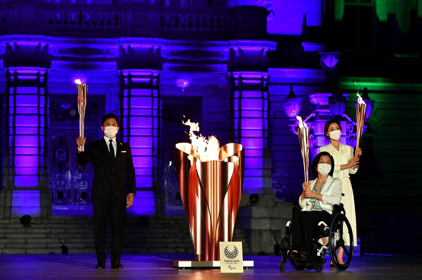 Tokyo 2020 Torch Relay Official Ambassadors Tadahiro Nomura (L), Aki Taguchi (2nd R), Satomi Ishihara (R) take part in the Paralympic Flame Lighting Ceremony at the State Guest House Akasaka Palace, Tokyo, Japan, Aug. 20, 2021. (AFP Photo)