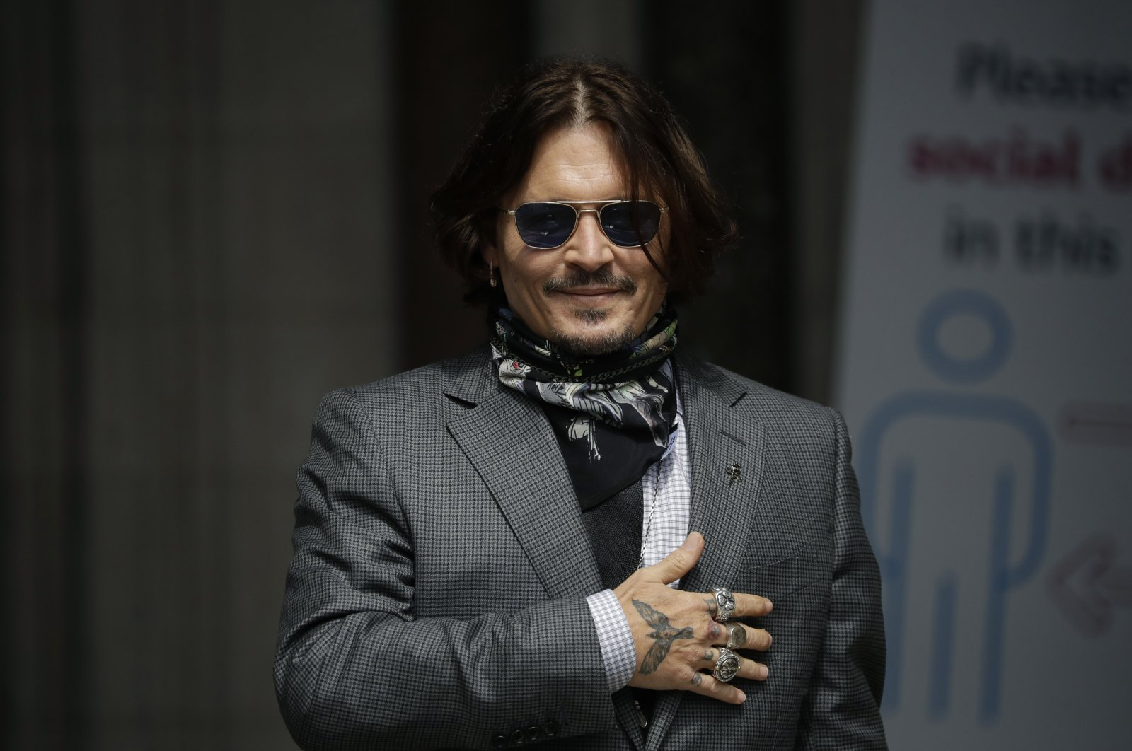 In this Thursday, July 23, 2020 file photo, U.S. actor Johnny Depp gestures to fans and the media as he arrives at the High Court in London. (AP Photo)