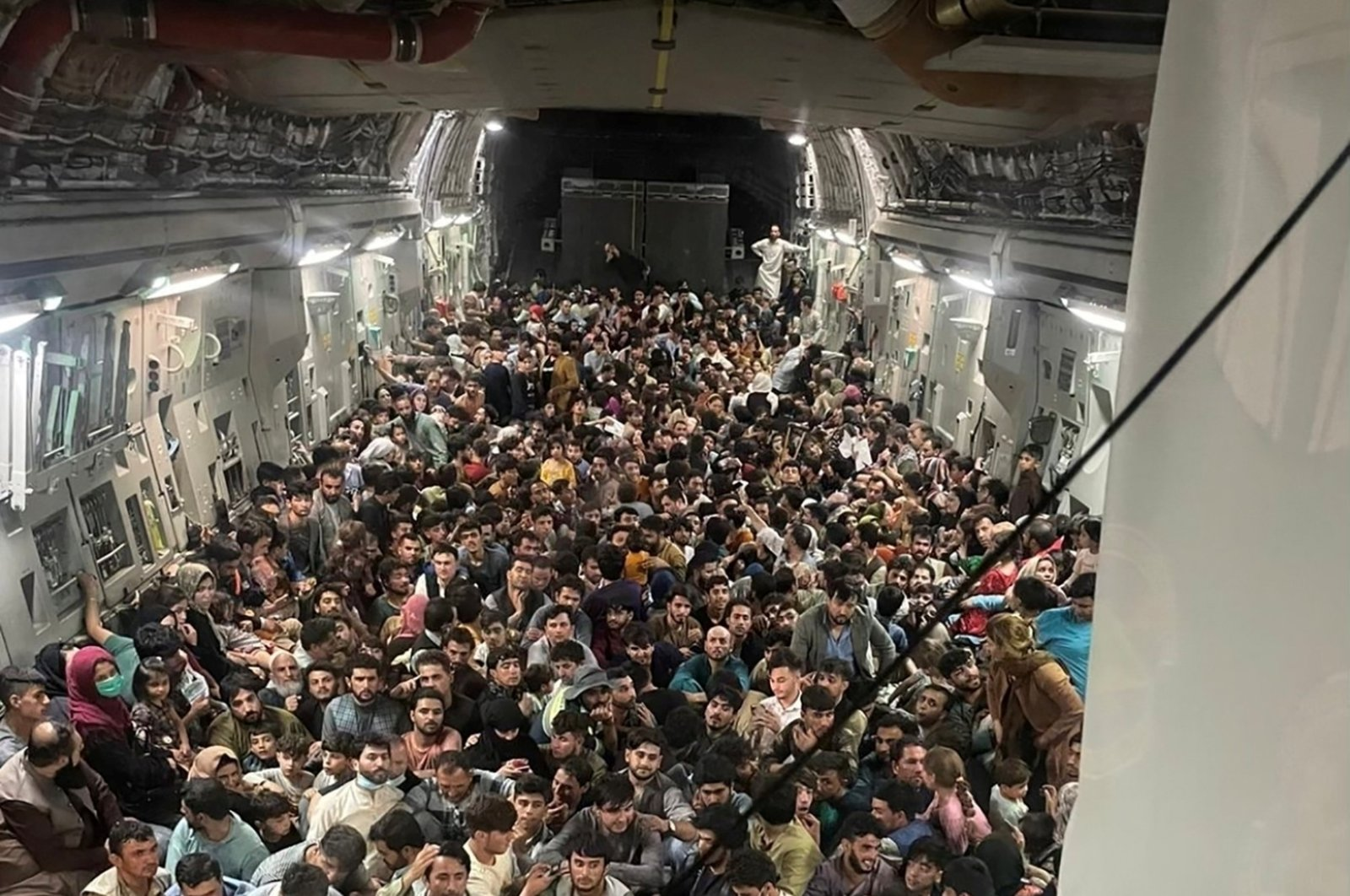 Evacuees crowd the interior of a U.S. Air Force C-17 Globemaster III transport aircraft, now known to have been carrying 823 Afghans to Qatar from Kabul, Afghanistan, Aug. 15, 2021.(U.S. Air Force/Handout via Reuters)