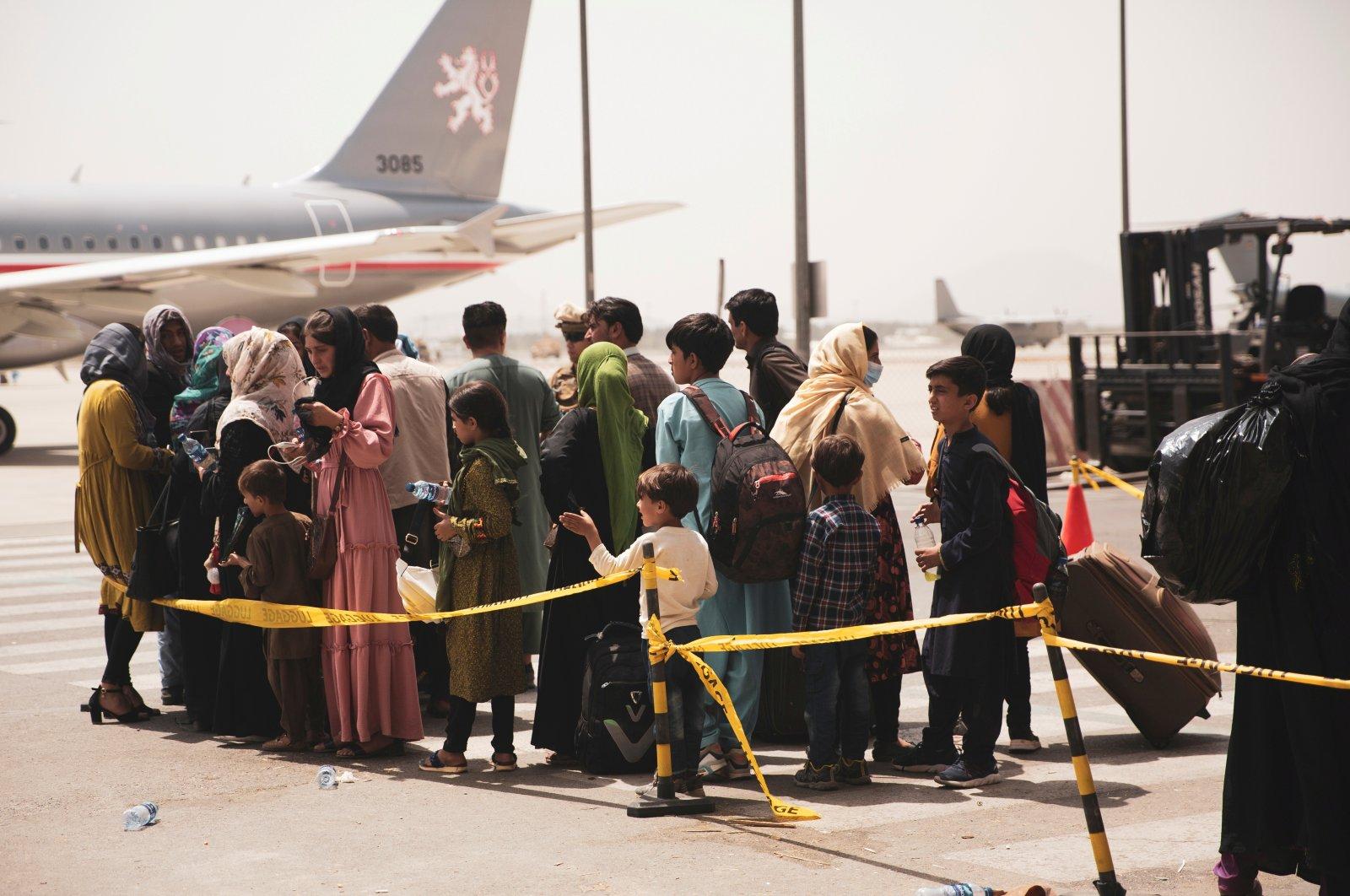 Civilians prepare to board a plane during an evacuation at Hamid Karzai International Airport, Kabul, Afghanistan, Aug. 18, 2021. (Reuters Photo)