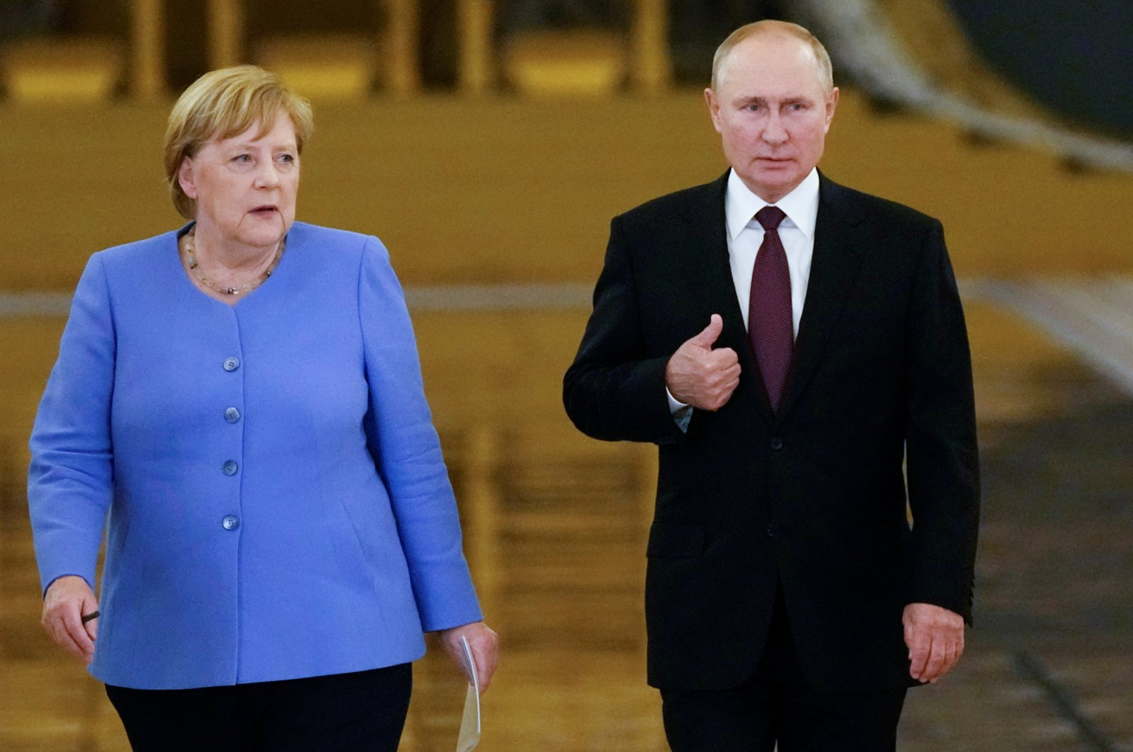 Russian President Vladimir Putin (R) and German Chancellor Angela Merkel (L) enter a hall during a news conference following their talks at the Kremlin in Moscow, Russia, Aug. 20, 2021. (Alexander Zemlianichenko / Pool via Reuters)
