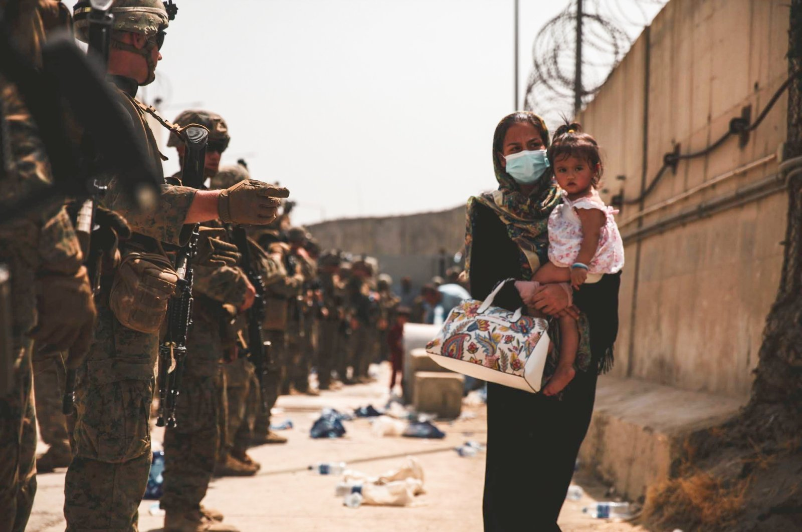 A U.S. Marine assigned to 24th Marine Expeditionary Unit guides an evacuee during an evacuation at Hamid Karzai International Airport, in Kabul, Afghanistan, Aug. 18, 2021. (Reuters Photo)