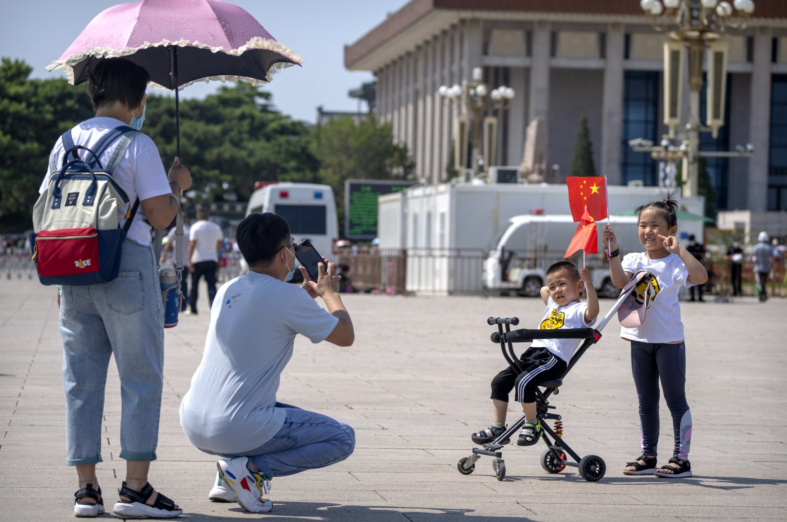 Children hold Chinese flags as they pose for a photo at Tiananmen Square in Beijing, June 22, 2021. (AP Photo)
