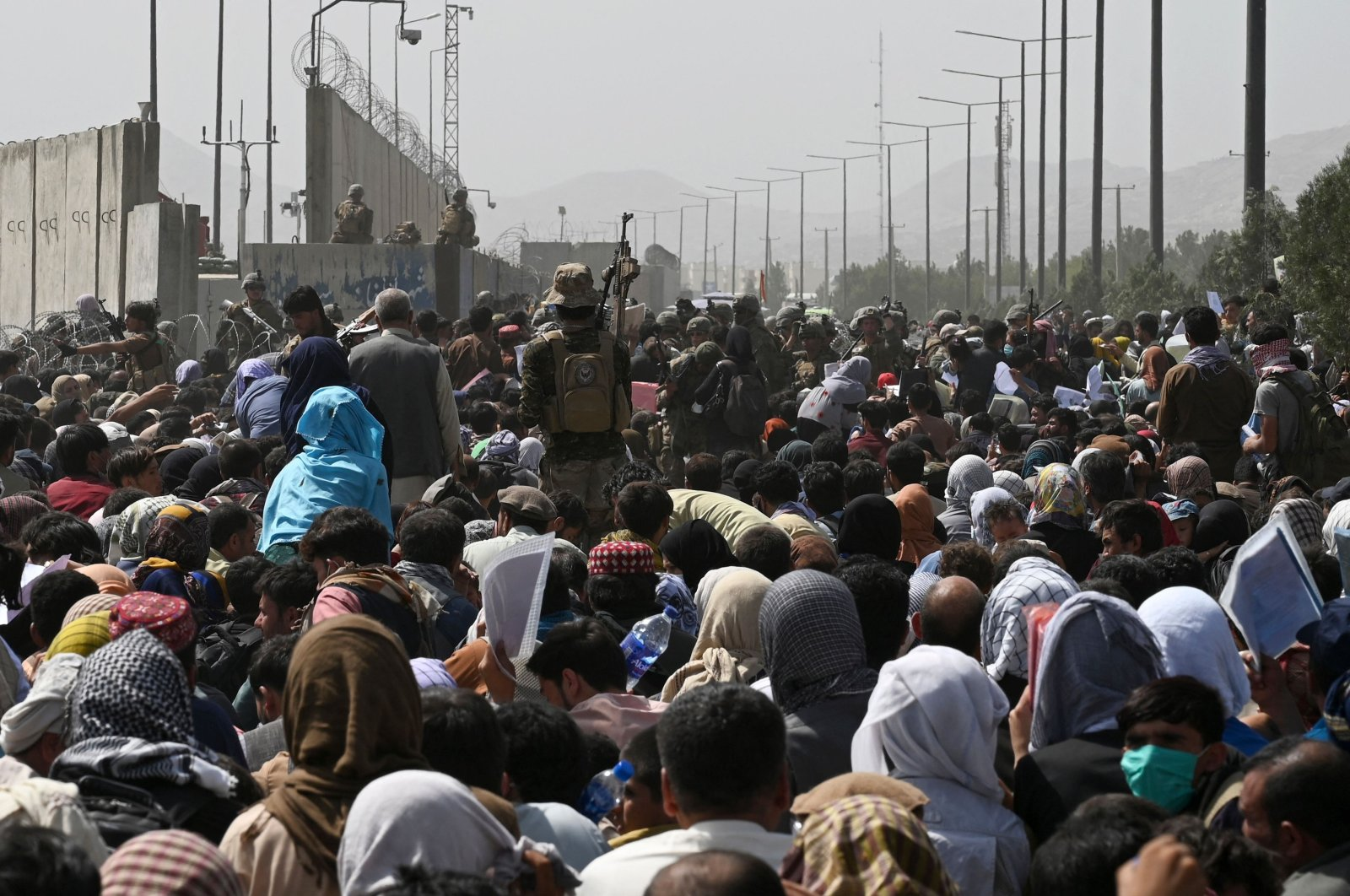 Afghans gather on a roadside near the military part of the airport in Kabul, Afghanistan, Aug. 20, 2021, hoping to flee from the country after the Taliban's military takeover. (AFP Photo)