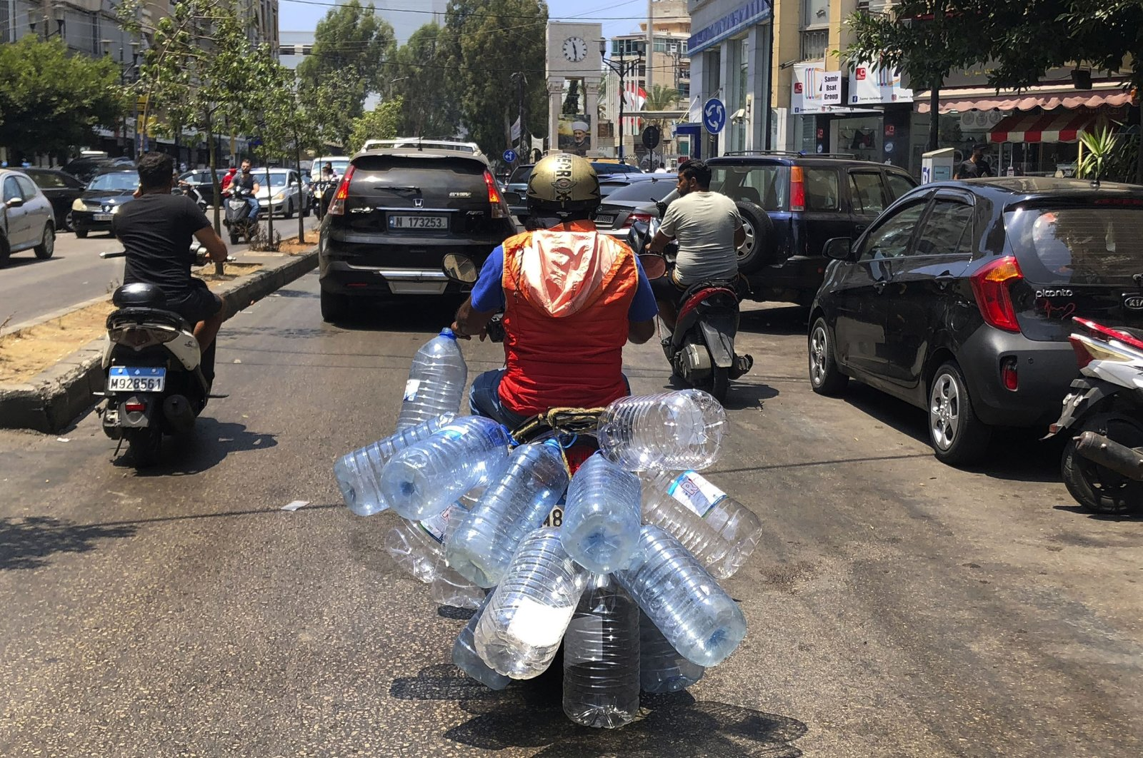 A man rides his scooter with empty water bottles, in Beirut, Lebanon, June 23, 2021. (AP Photo)