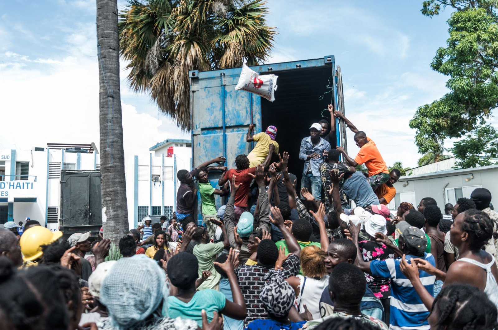 """A man throws a bag of rice into a crowd of earthquake victims gathered for the distribution of food and water at the """"4 Chemins"""" crossroads in Les Cayes, Haiti, Aug. 20, 2021. (AFP Photo)"""