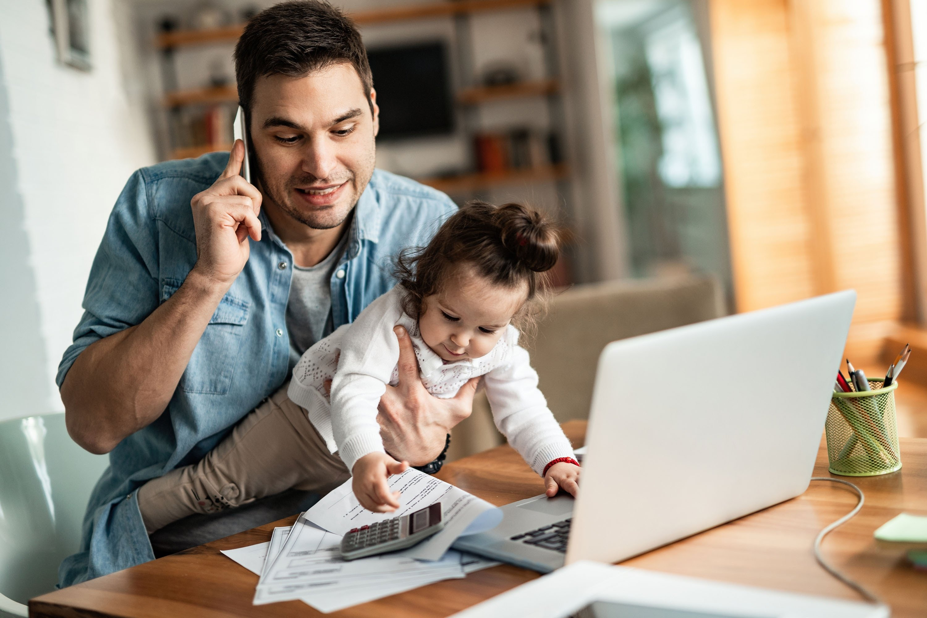 A father talking on the phone during a home office day while babysitting at the same time. (Shutterstock Photo)