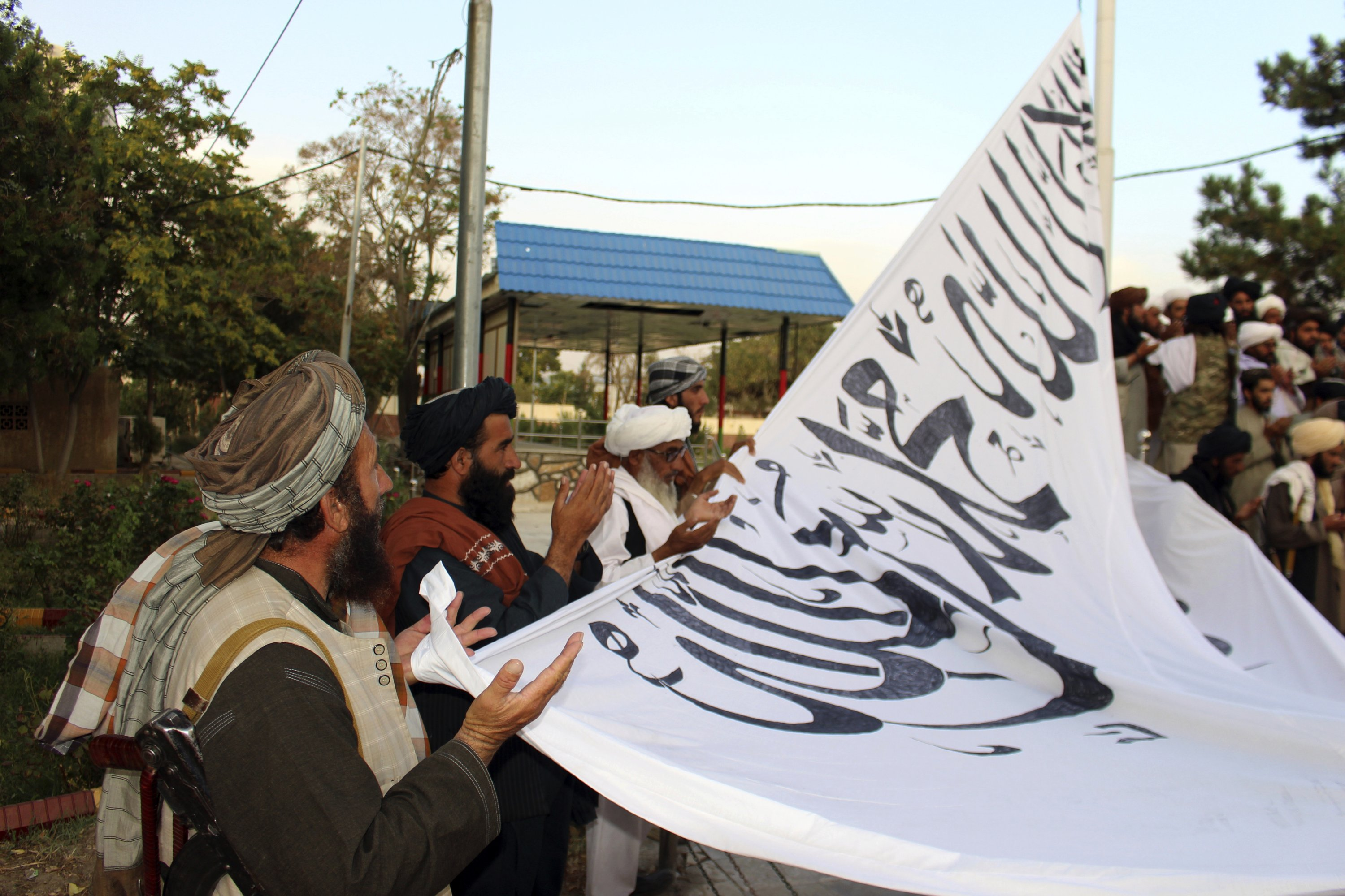 Taliban fighters pray while raising their flag at the Ghazni provincial governor's house, in Ghazni, southeastern Afghanistan, Aug. 15, 2021. (AP Photo)