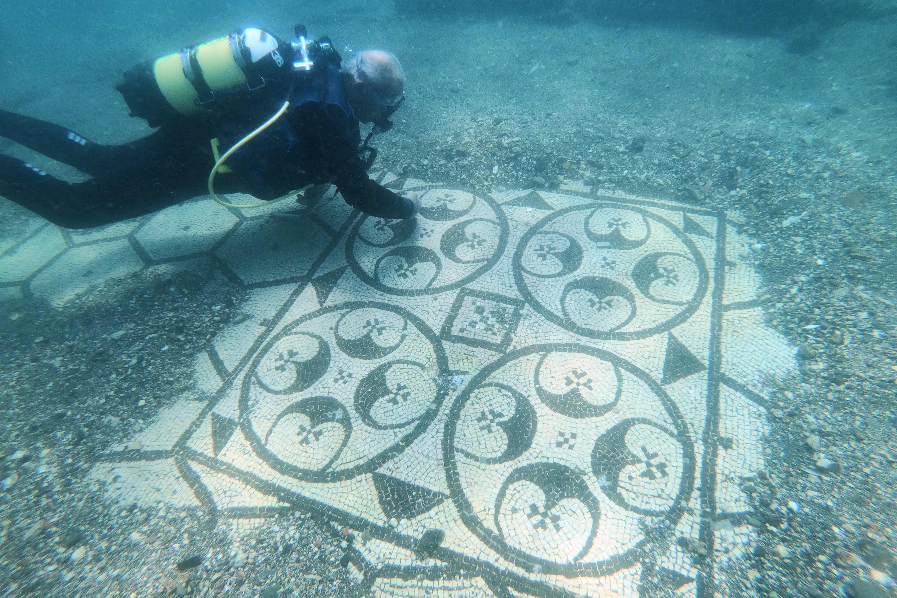 A dive guide shows tourists a mosaic of Villa a Protiro, in the ancient submerged Roman city of Baiae, in Pozzuoli, near Naples, Italy on August 18, 2021 (AFP photo)