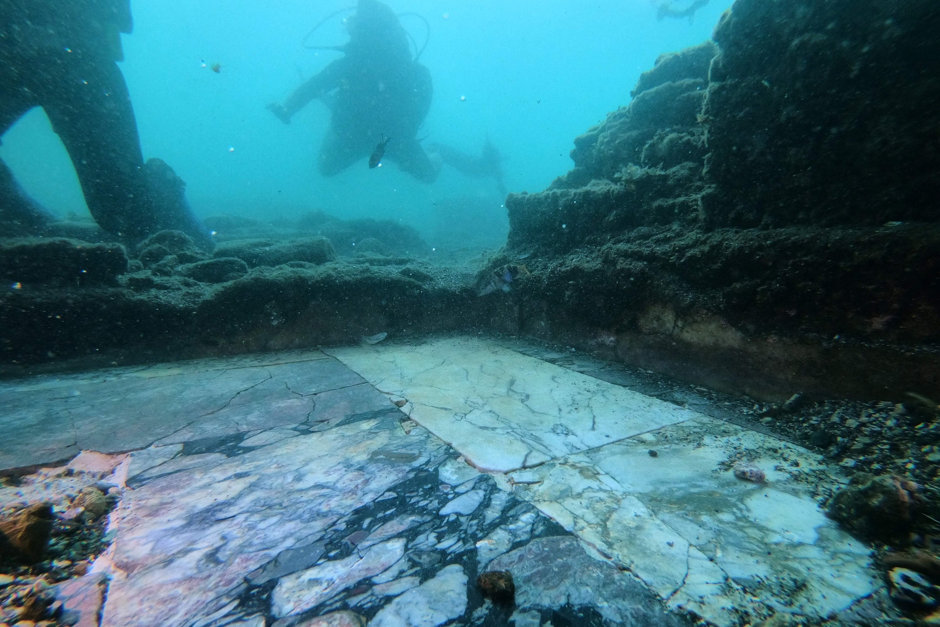 A dive guide shows tourists a Roman marble of the thermal building of the Nymphaeum of punta Epitaffio, in the submerged ancient Roman city of Baiae, Pozzuoli near Naples, Italy, Aug. 18, 2021. (AFP Photo)