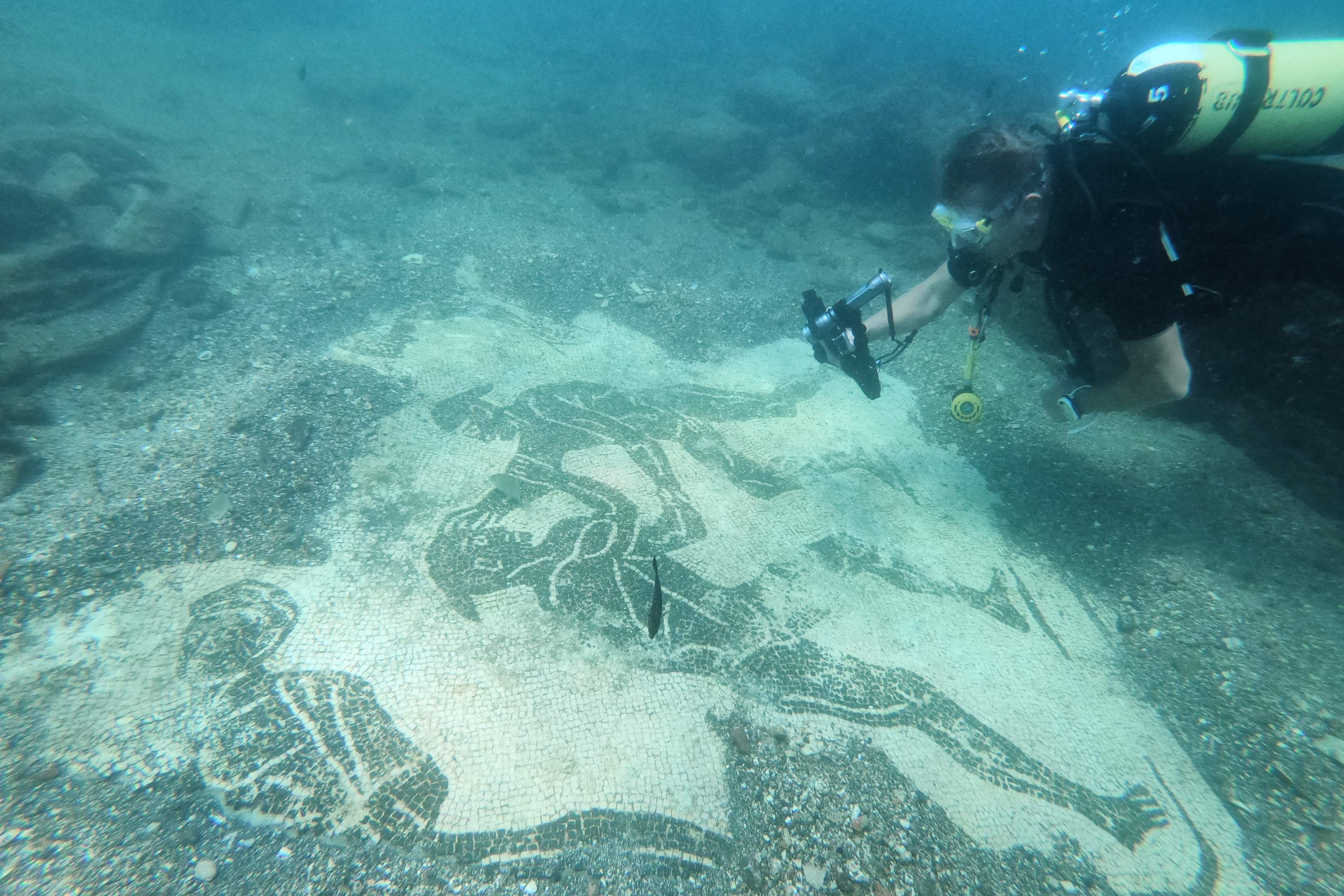 A dive guide shows tourists a mosaic from Villa a Protiro, in the submerged ancient Roman city of Baiae, Pozzuoli near Naples, Italy, Aug. 18, 2021. (AFP Photo)