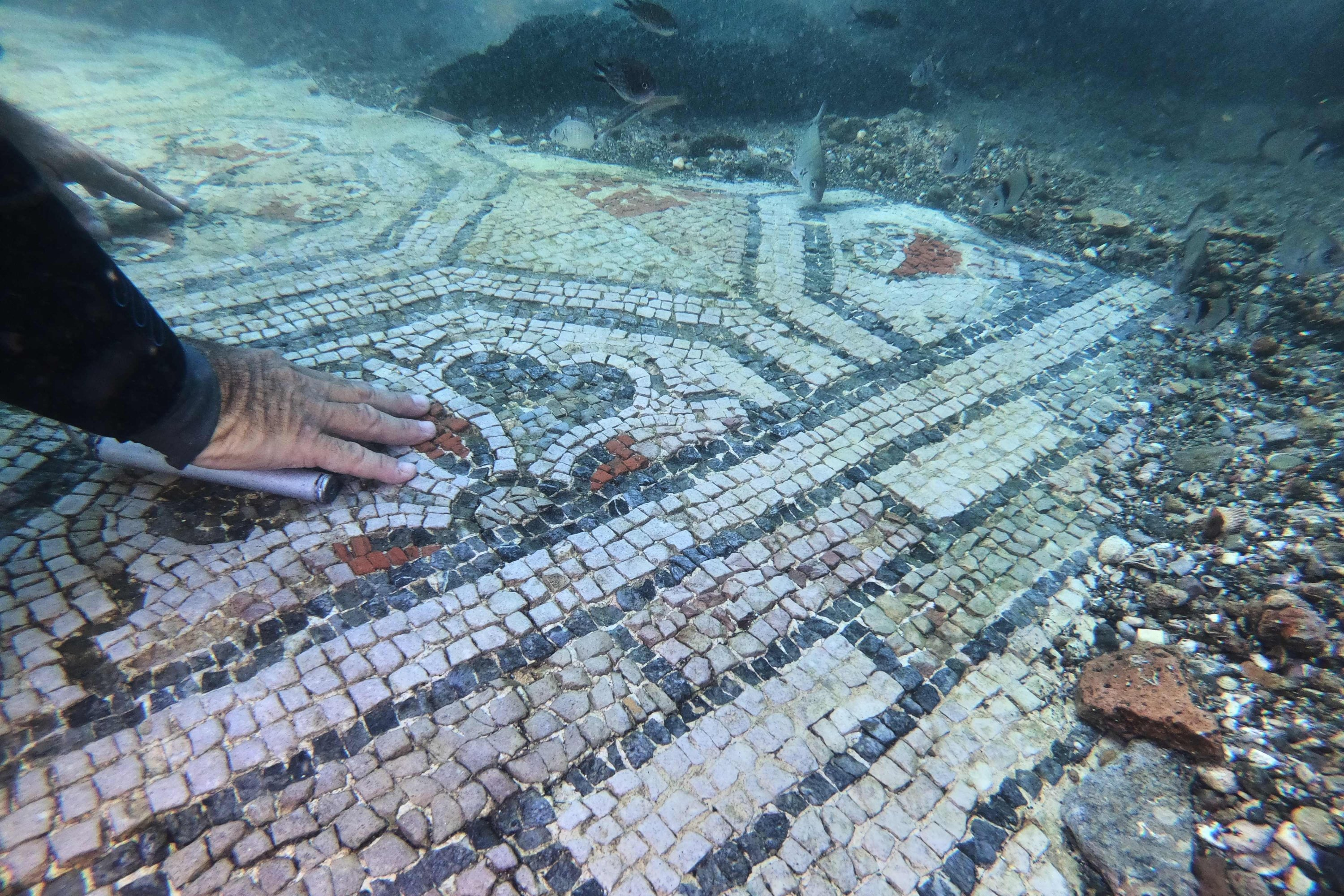 A dive guide shows tourists a mosaic from Terme del Lacus, in the submerged ancient Roman city of Baiae, Pozzuoli near Naples, Italy, Aug. 18, 2021. (AFP Photo)