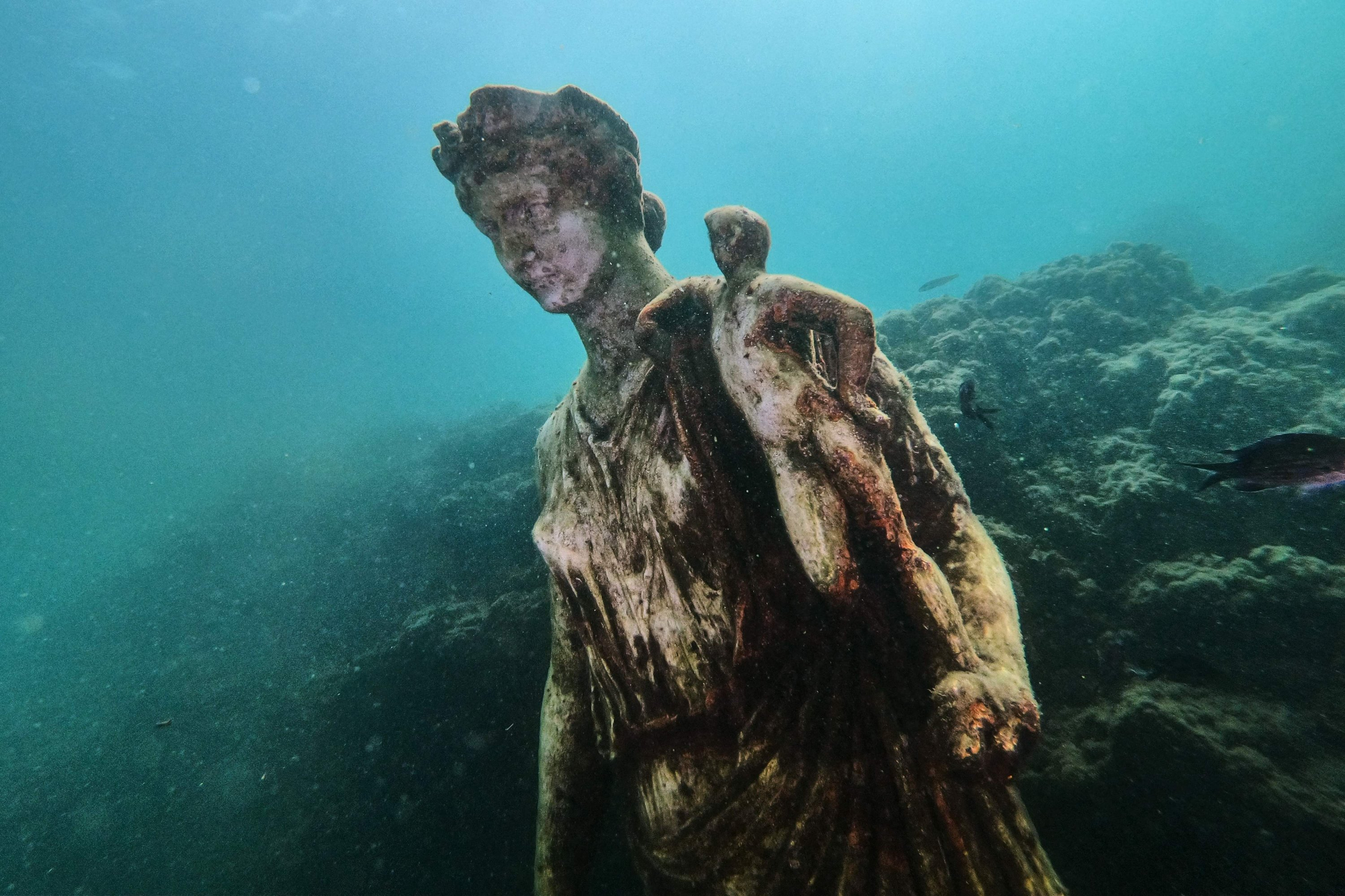Fish swim past a copy of the original statue preserved at the Museum of Baiae, Pozzuoli near Naples, Italy, Aug. 18, 2021. (AFP Photo)