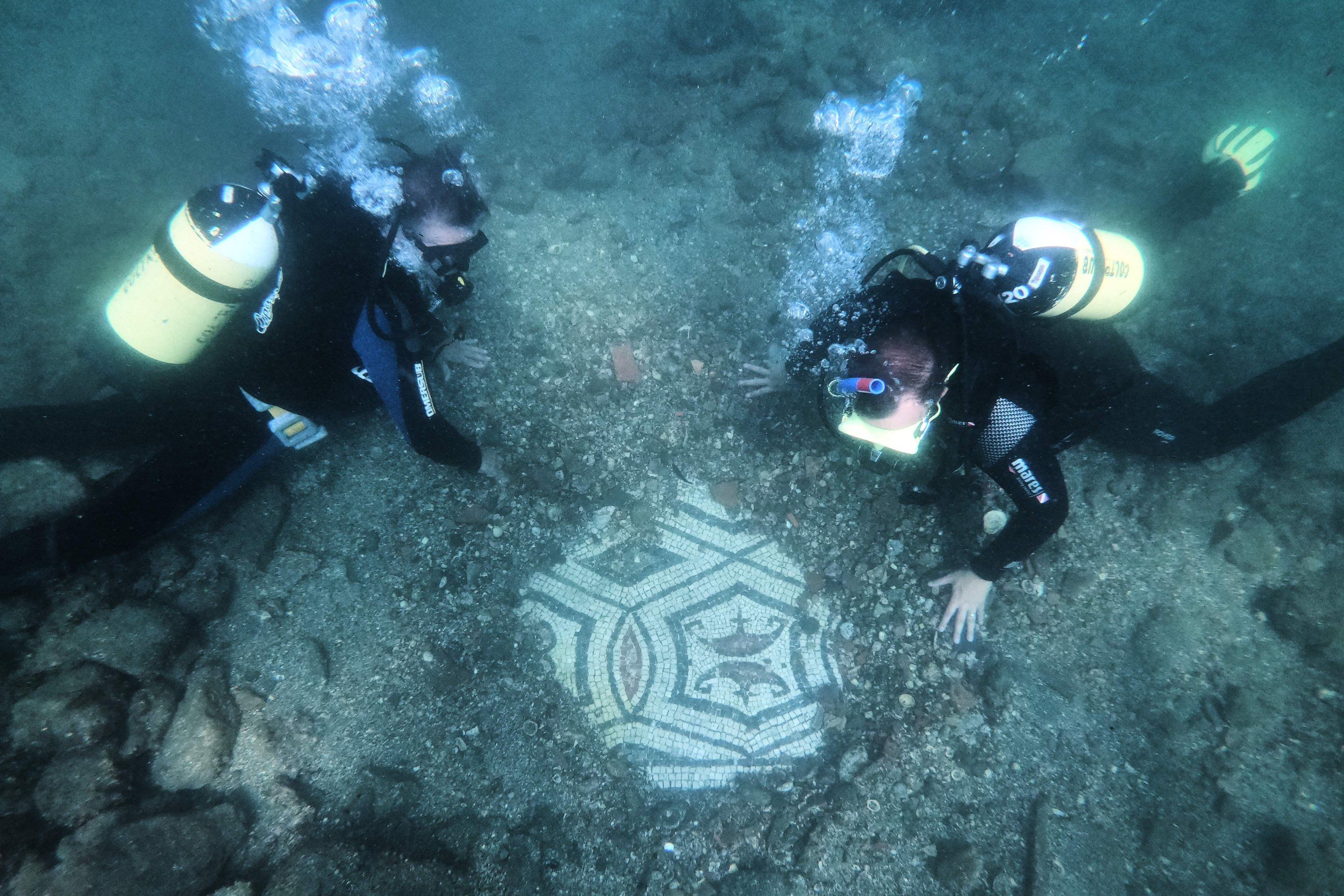 A dive guide shows tourists a mosaic of Terme del Lacus, in Pozzuoli, near Naples, Italy, August 18, 2021 (AFP photo)