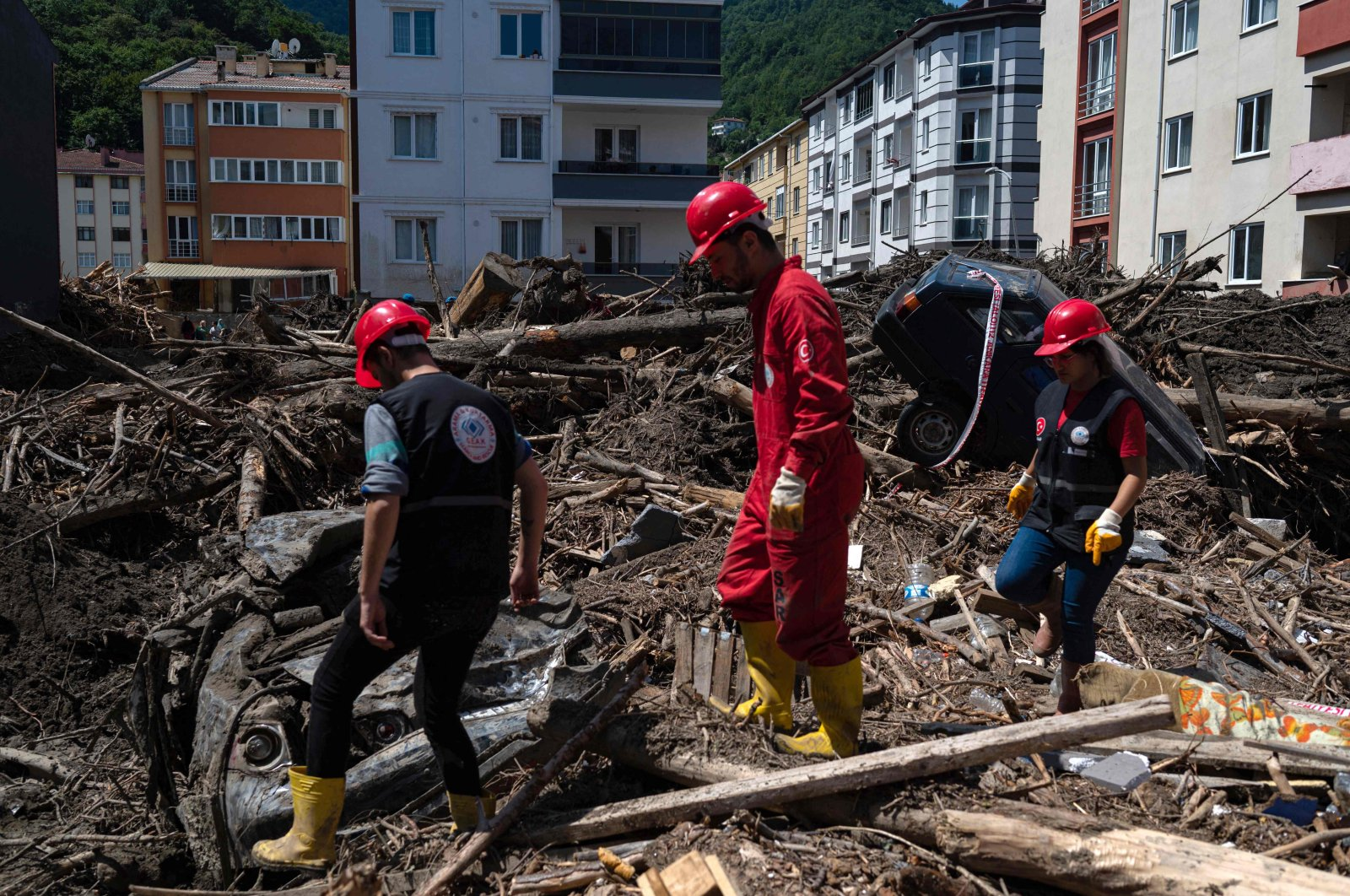 Civil defense workers walk through the mud and debris after flash floods destroyed parts of the town of Bozkurt in the district of Kastamonu, in the Black Sea region of Turkey, Aug. 15, 2021. (AFP Photo)