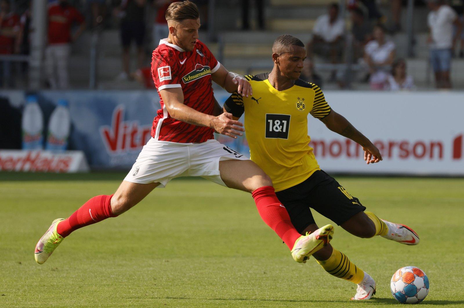 Freiburg's Ermedin Demirovic (L) in action against Dortmund's Manuel Akanji (R) during a German Bundesliga match in Freiburg, Germany, Aug. 21, 2021. (EPA Photo)