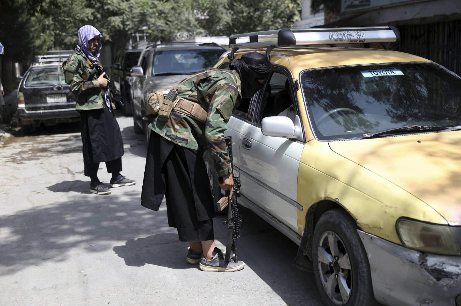 Taliban fighters search a vehicle at a checkpoint on the road in the Wazir Akbar Khan neighborhood in the city of Kabul, Afghanistan, Sunday, Aug. 22, 2021. (AP Photo)