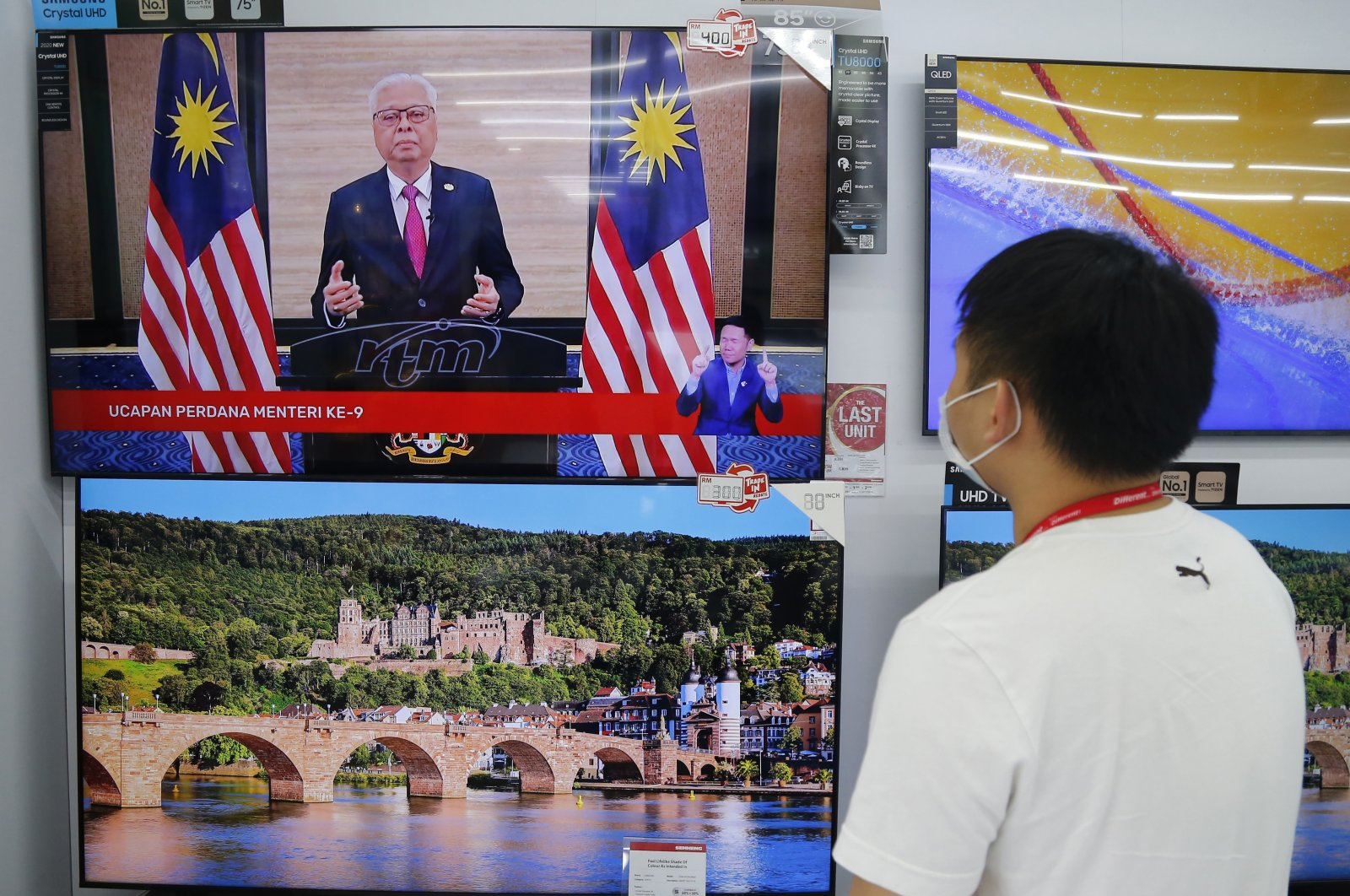 An electronic shop worker watches a speech by Malaysia's new Prime Minister Ismail Sabri Yaakob on television in Shah Alam, Malaysia, Aug. 22, 2021. (AP Photo)