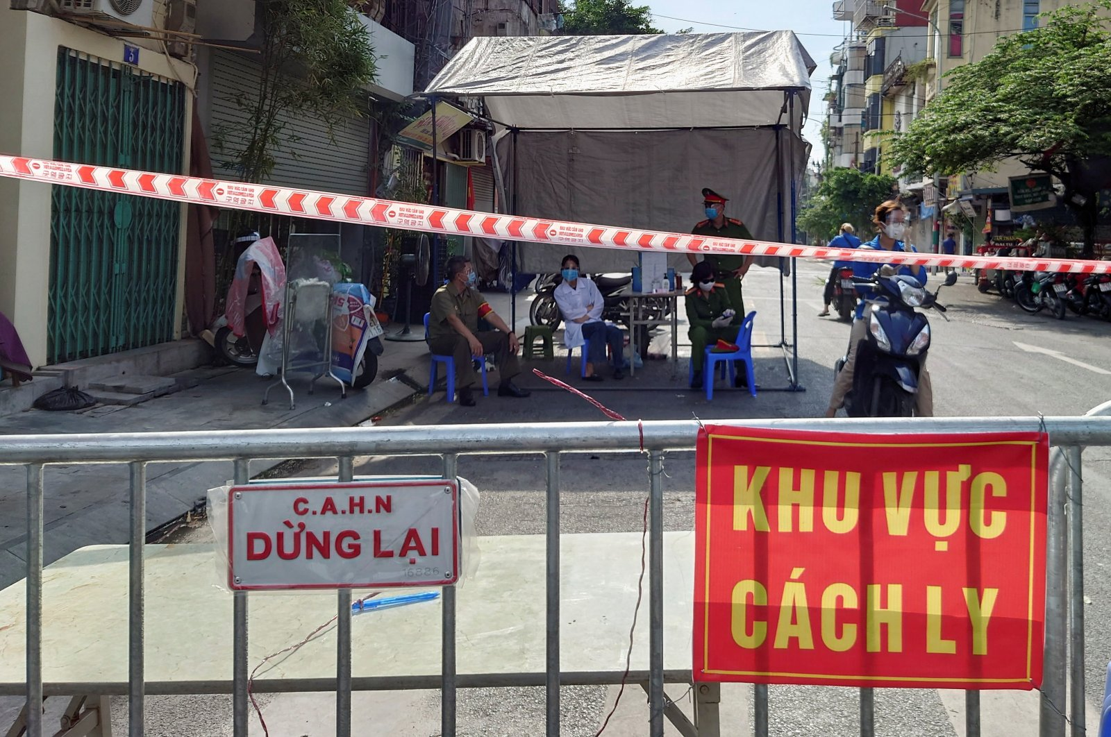 """Signs reading """"Hanoi Police - Stop"""" and """"Quarantine Area"""" are seen next to a street barricade set up as the country imposes measures to prevent the spread of the coronavirus disease (COVID-19), in Hanoi, Vietnam, Aug. 22, 2021. (REUTERS Photo)"""