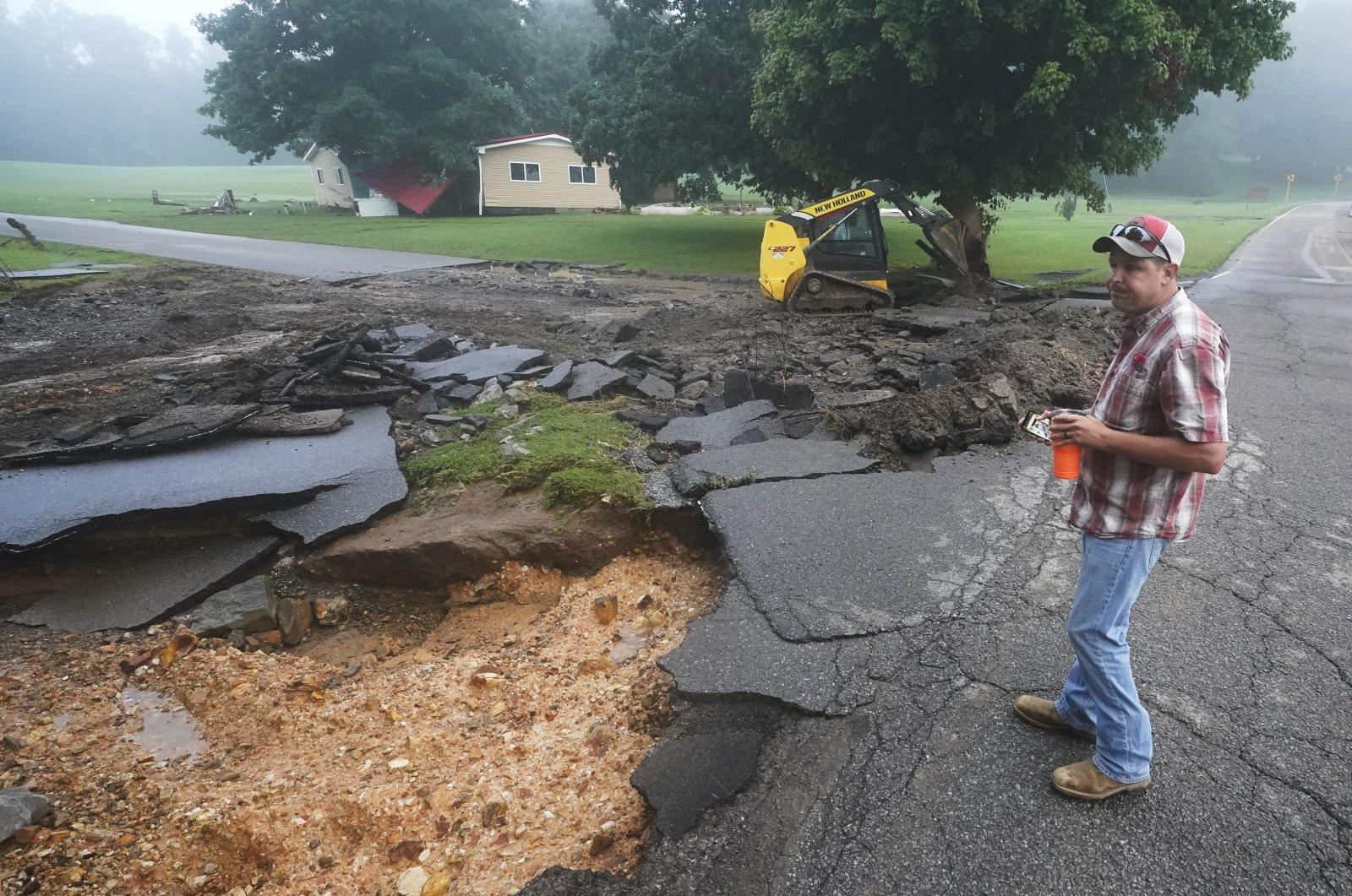 Michael Pate watches as a road is repaired in McEwen, Tenn., U.S., Aug. 22, 2021. (AP Photo)