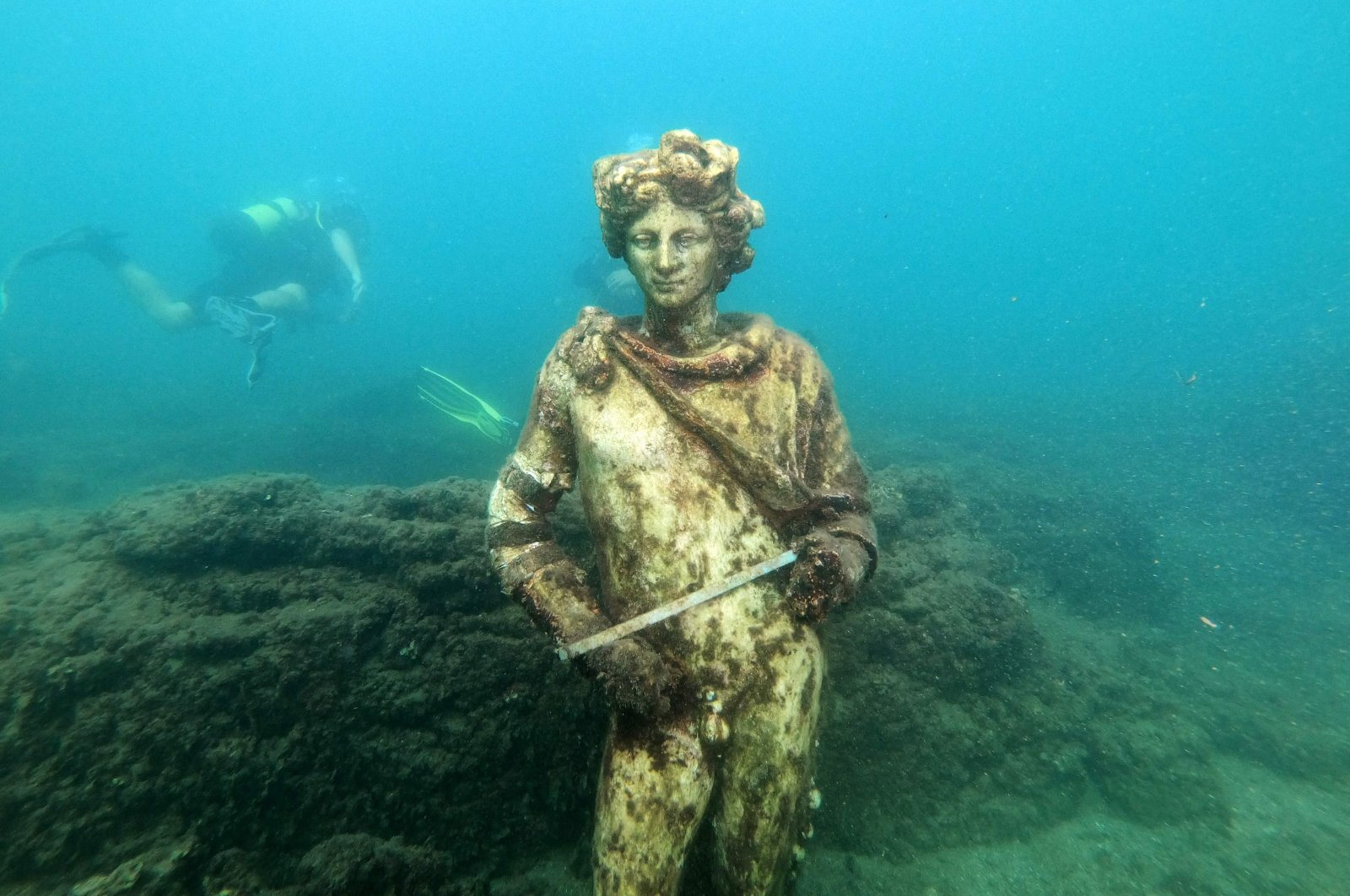 A dive guide shows tourists a copy of the original statue preserved at the Museum of Baiae in the submerged ancient Roman city of Baiae, Pozzuoli near Naples, Italy, Aug. 18, 2021. (AFP Photo)