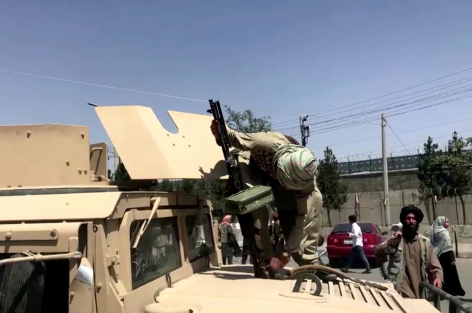 A Taliban fighter on top of an armoured vehicle loads a gun outside the airport in Kabul, Afghanistan Aug. 16, 2021. (Reuters File Photo)