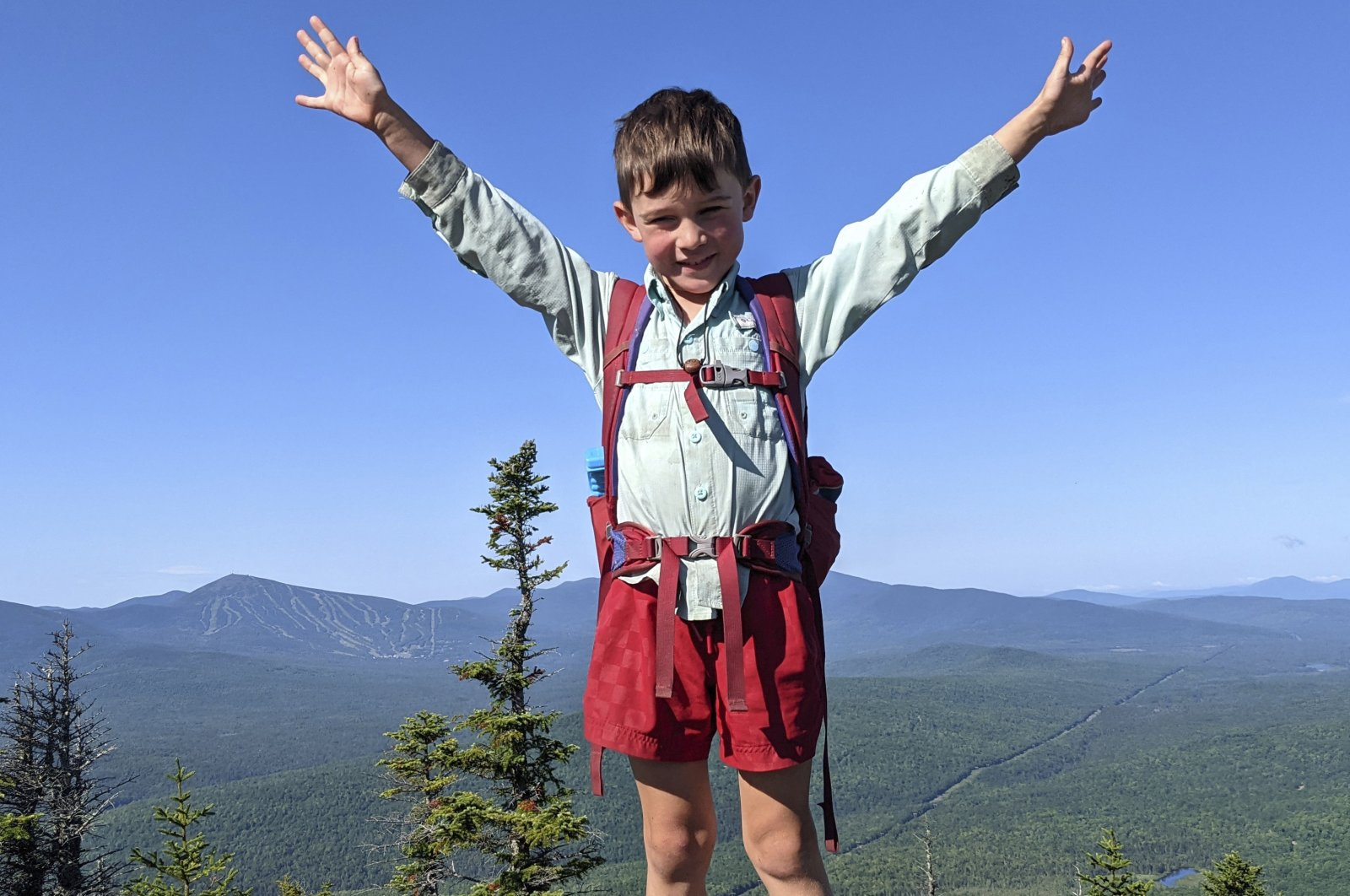 5-year-old Harvey Sutton raises his arms on a mountain top in Bigelow Preserve while hiking the Appalachian Trail, Maine, U.S., July 23, 2021. (AP Photo)