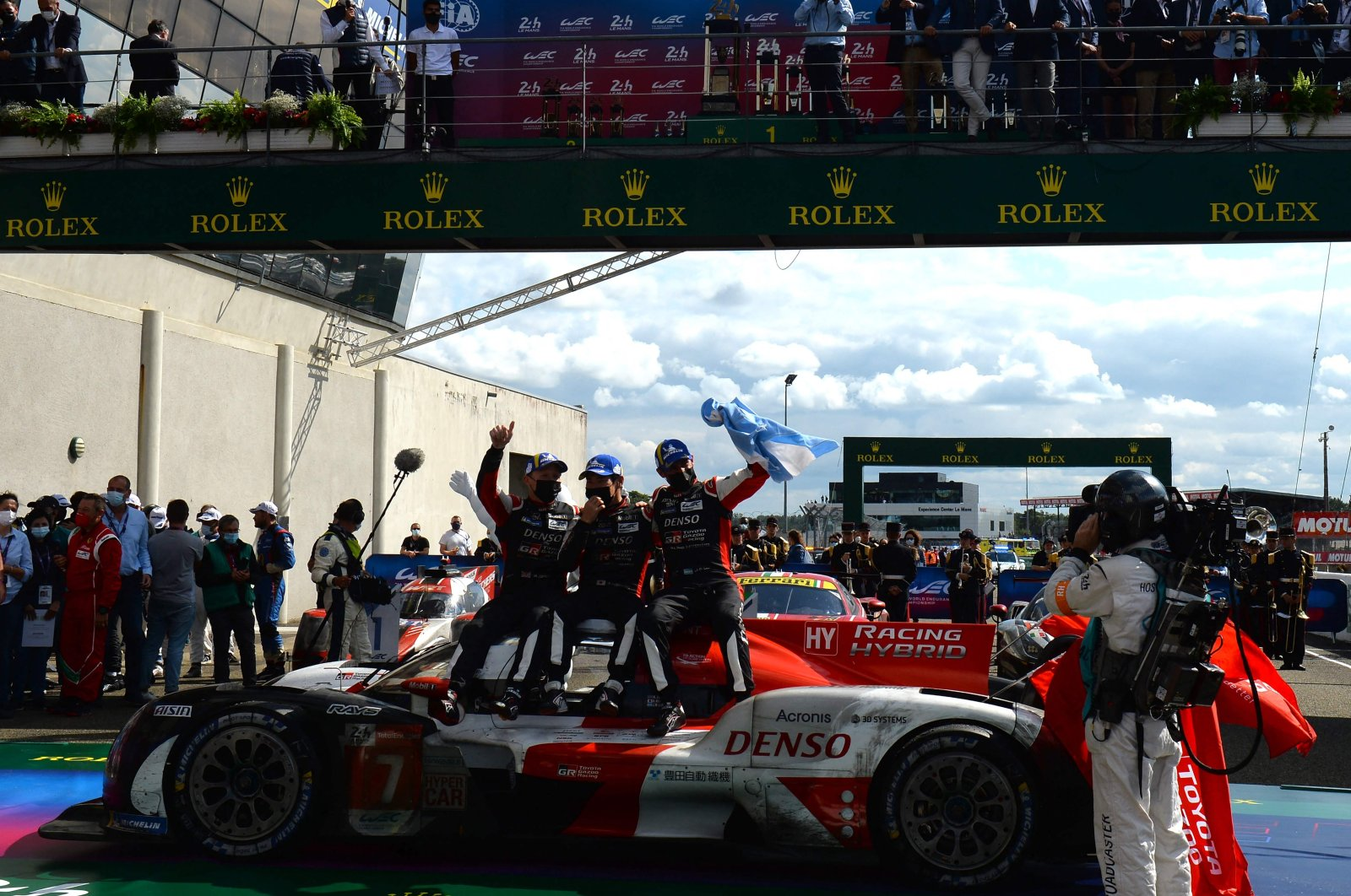 Toyota's British driver Mike Conway (L), Japanese driver Kamui Kobayashi (C) and Argentine driver Jose Maria Lopez celebrate after winning the 89th edition of the Le Mans 24 Hours endurance race, in Le Mans, northwestern France, Aug. 22, 2021. (AFP Photo)