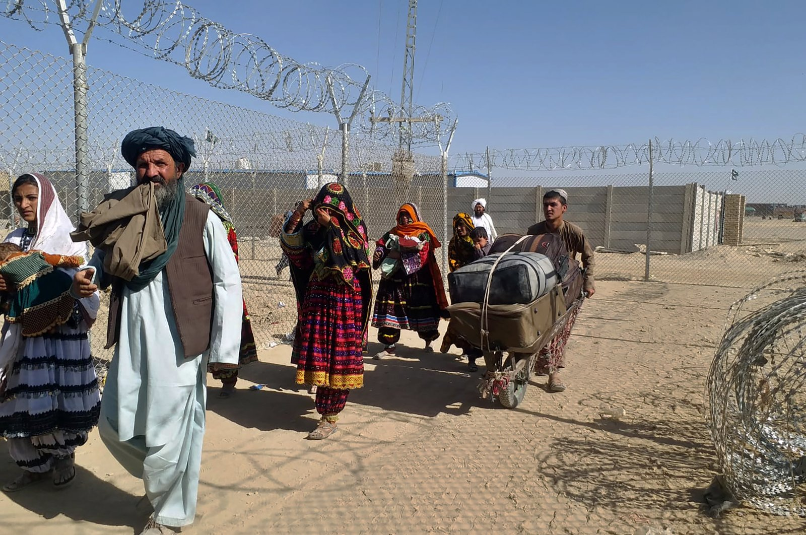 Afghan families enter Pakistan through a border crossing point in Chaman, Pakistan, Sunday, Aug. 22, 2021. (AP Photo)