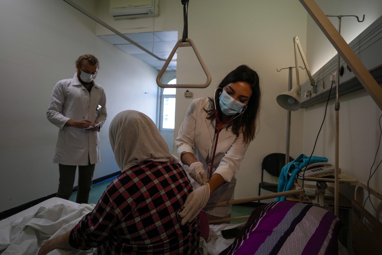 Ghaidaa al-Saddik, an internal medicine resident, checks on a patient at government-run Rafik Hariri University Hospital in Beirut, Lebanon, Aug. 11, 2021. (AP Photo)