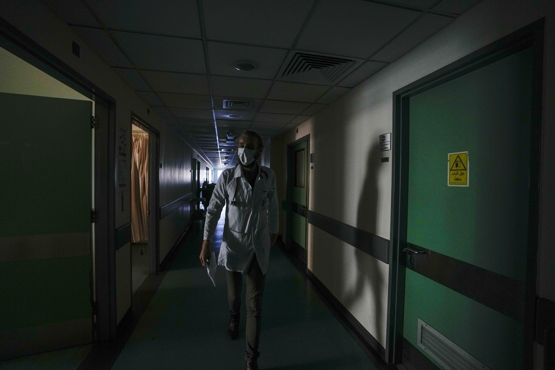 A doctor walks through a corridor of the government-run Rafik Hariri University Hospital during a power outage in Beirut, Lebanon, Aug. 11, 2021. (AP Photo)