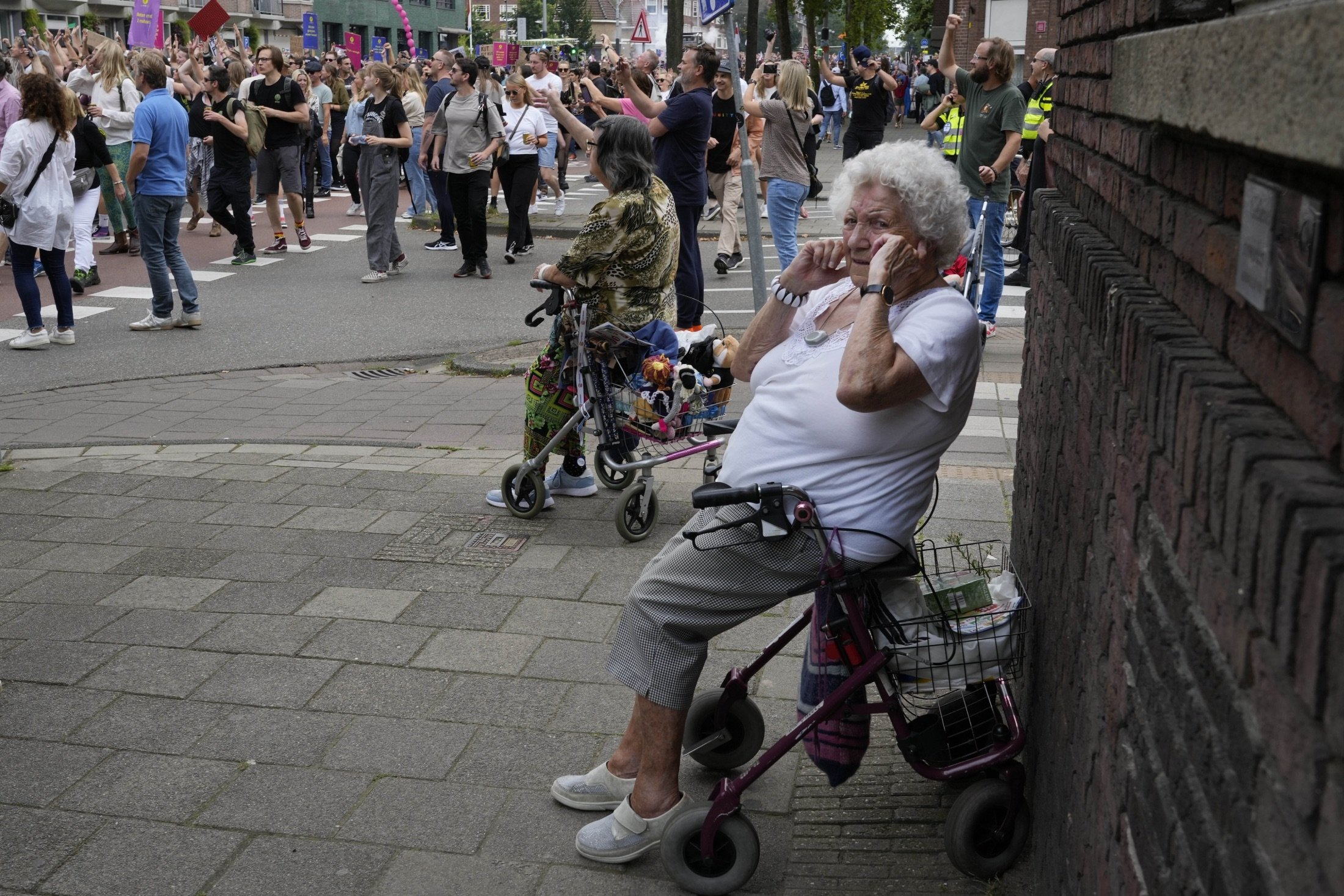An older woman shields her ears during a protest of organizers and fans of music festivals stage against the government's COVID-19 restrictions on large-scale outdoor events, in Amsterdam, Netherlands, Aug. 21, 2021. (AP Photo)