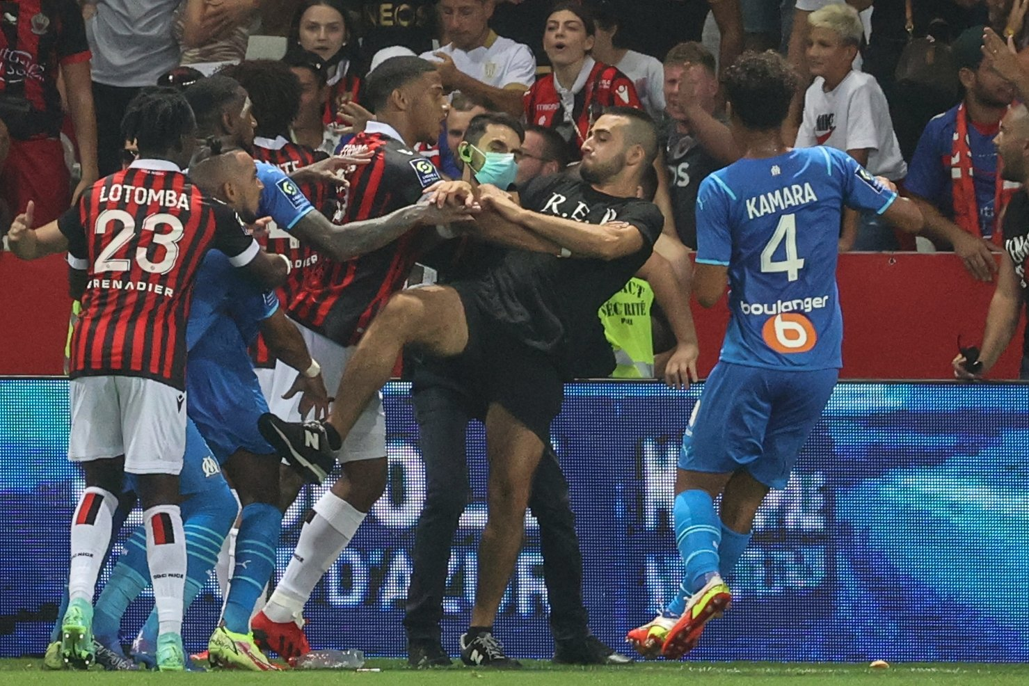 Marseille's French midfielder Dimitri Payet (2nd L) reacts as players from OGC Nice (red and black jersey) and Olympique de Marseille (blue jersey) stop a fan invading the pitch trying to kick Payet during Ligue 1 match at the Allianz Riviera stadium in Nice, southern France, Aug. 22, 2021. (AFP Photo)