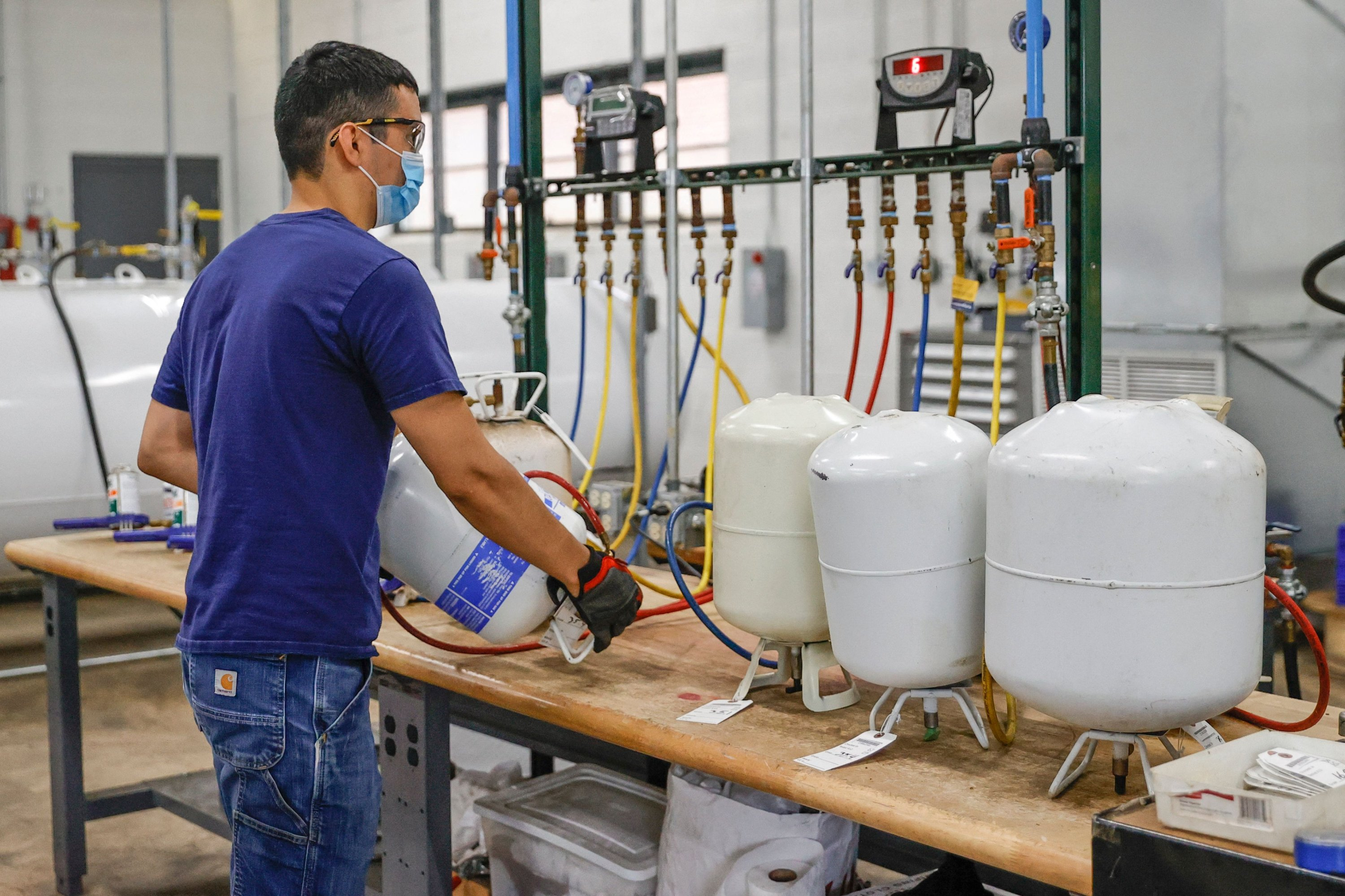 Employee Victor Molina empties used refrigerants at the Tradewater Refrigerant Solutions Warehouse in Elk Grove Village, Illinois, U.S., Aug. 11, 2021. (AFP Photo)