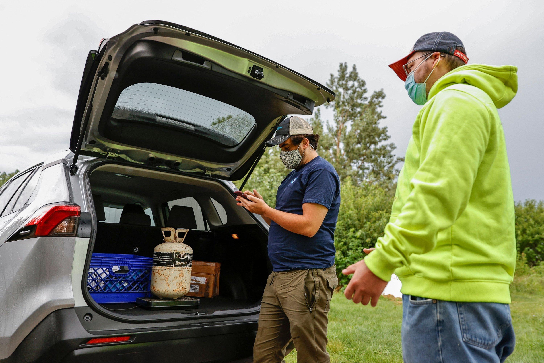 Chad Dorger (L), senior environmental program associate at Tradewater Refrigerant Solutions, picks up empty refrigerant tanks from Rick Karas (R) in Peotone, Illinois, U.S., Aug. 11, 2021. (AFP Photo)